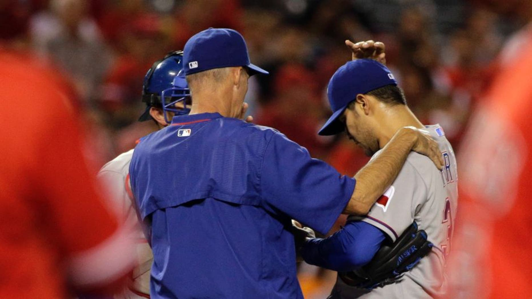 Texas Rangers pitching coach Mike Maddux, center, confers with starting pitcher Martin Perez, center right, and catcher Bobby Wilson after Perez walked Los Angeles Angels' Albert Pujols, foreground right, during the third inning of a baseball game, Friday, Sept. 4, 2015, in Anaheim, Calif. (AP Photo/Jae C. Hong)