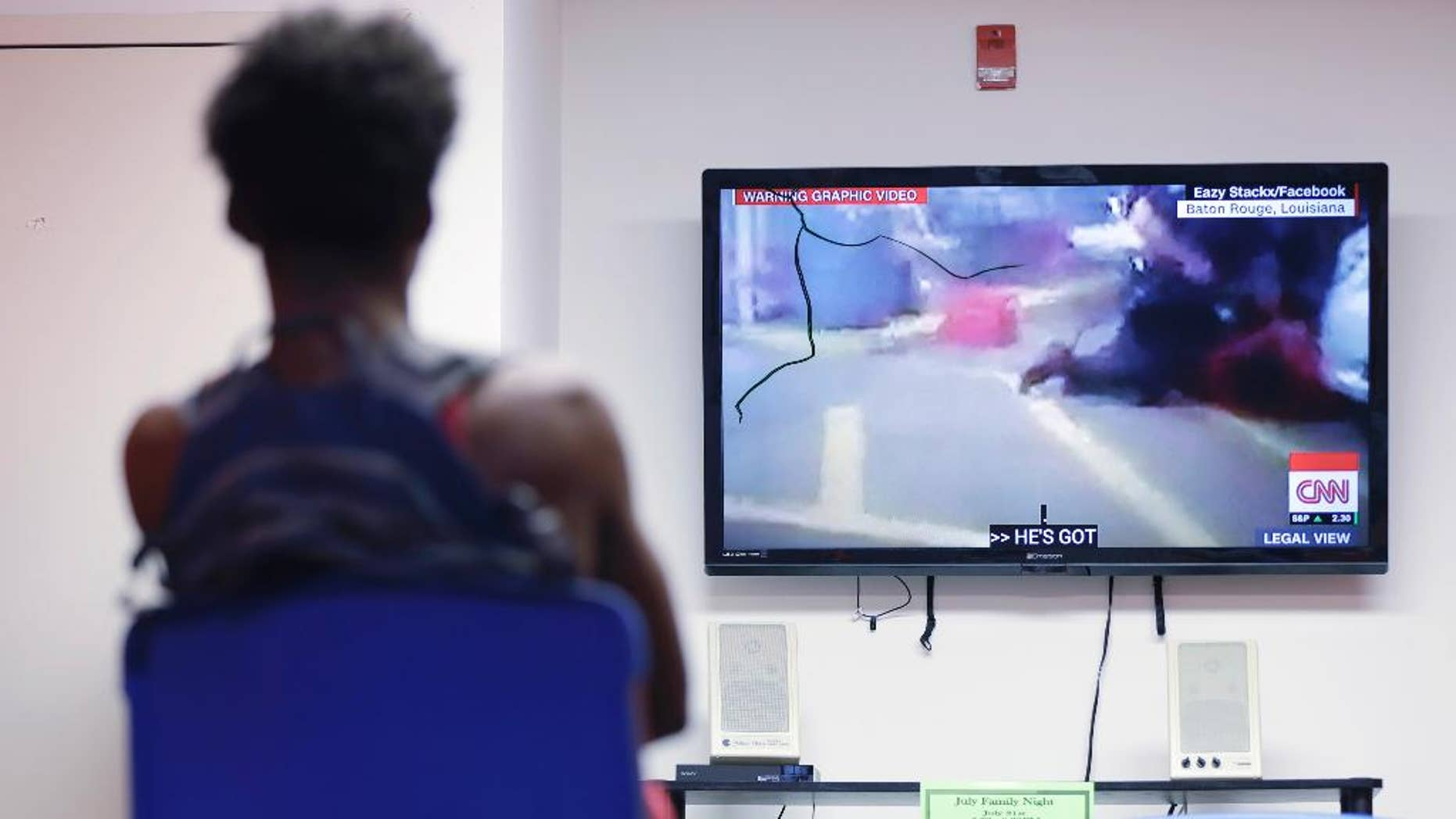 In this July 6, 2016, photo, a teen views a recording of the fatal police involved shooting in Louisiana, during a weekly mentoring meeting at The Bridge, a youth intervention and diversion program in Philadelphia. A group of black boys met with their mentors in Philadelphia to discuss one of the latest incidents at the start of what would be a week of violence ending with two black men dead and five Dallas police officers killed by a sniper. (AP Photo/Matt Rourke)
