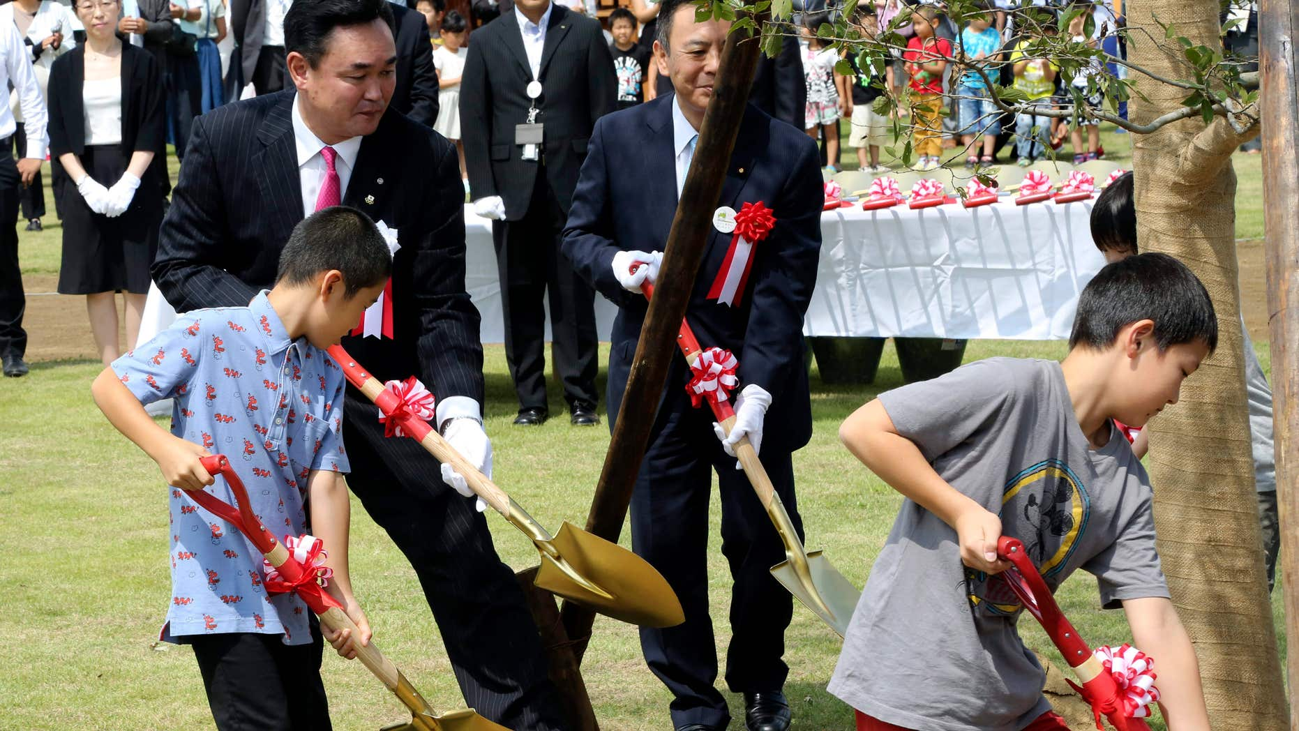 Sept. 5, 2015: Noraha Mayor Yukiei Matsumoto, rear left, plants a tree with children of Naraha residents during an event in Naraha, Fukushima, northern Japan.