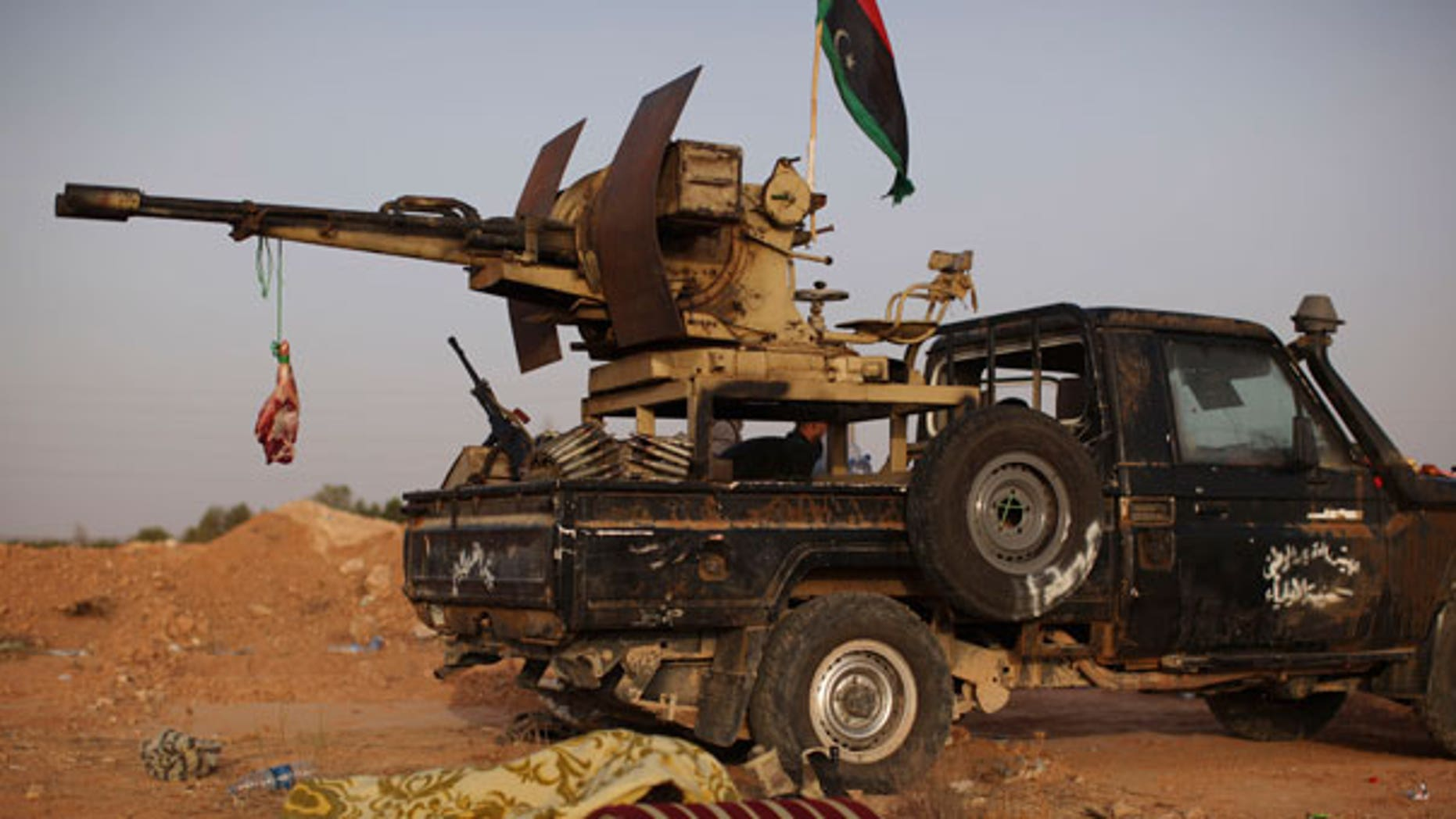 Sept. 5: A rebel fighter sleeps next to a goat's carcass hanging from an anti-aircraft gun at a checkpoint between Tarhouna and Bani Walid in Libya.