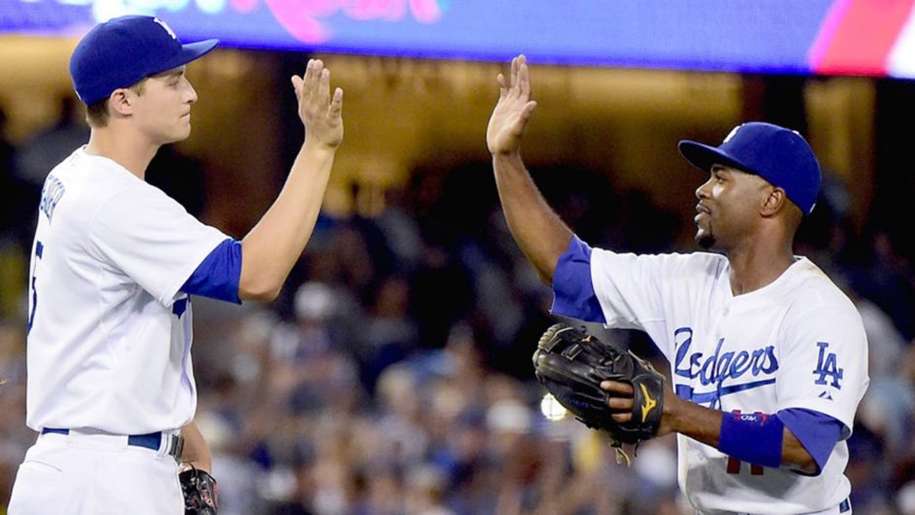 LOS ANGELES, CA - SEPTEMBER 23: Jimmy Rollins #11 of the Los Angeles Dodgers celebrates a 4-1 win over the Arizona Diamondbacks with Kenley Jansen #74 and Corey Seager #5 at Dodger Stadium on September 23, 2015 in Los Angeles, California. (Photo by Harry How/Getty Images)