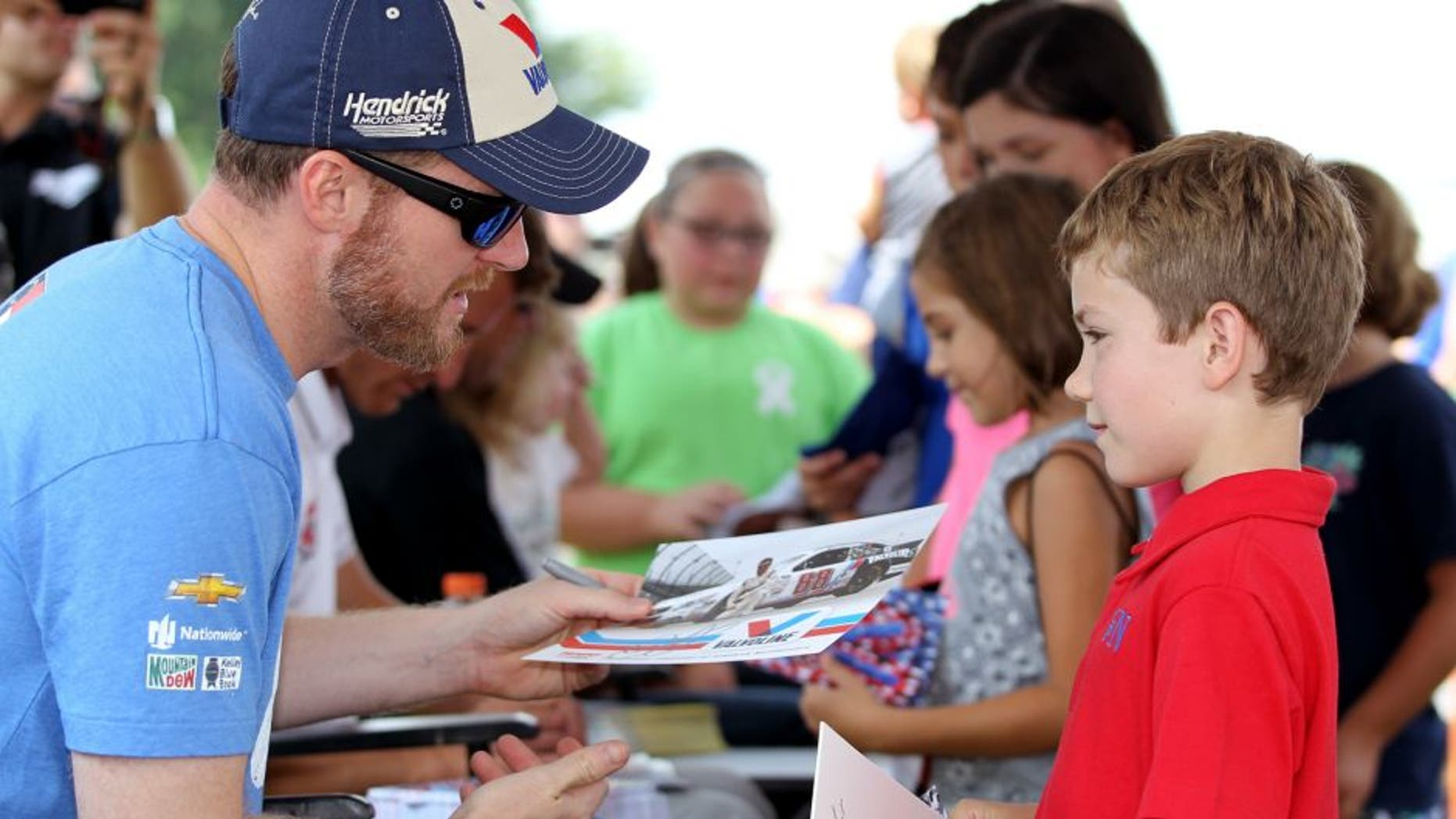 DARLINGTON, SC - SEPTEMBER 05: Dale Earnhardt Jr., driver of the #88 Valvoline Chevrolet, left, signs his autograph for young fans at an autgraph session prior to qualifying for the NASCAR Sprint Cup Series Bojangles' Southern 500 at Darlington Raceway on September 5, 2015 in Darlington, South Carolina. (Photo by Kena Krutsinger/Getty Images)