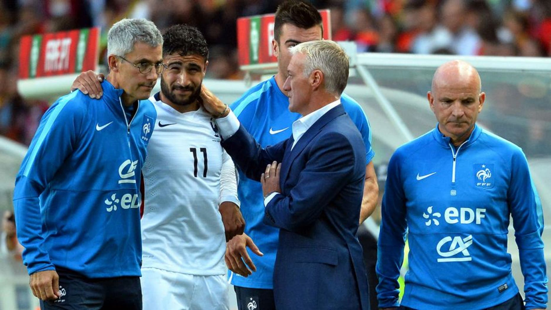France's forward Nabl Fekir (C) leaves the pitch after injury next to French doctor Franck Le Gall (L), head coach Didier Deschamps and assistant coach Guy Stephan during the Euro 2016 friendly football match Portugal vs France at the Jose Alvalade stadium in Lisbon on September 4, 2015. France won 0-1. AFP PHOTO/ FRANCK FIFE (Photo credit should read FRANCK FIFE/AFP/Getty Images)