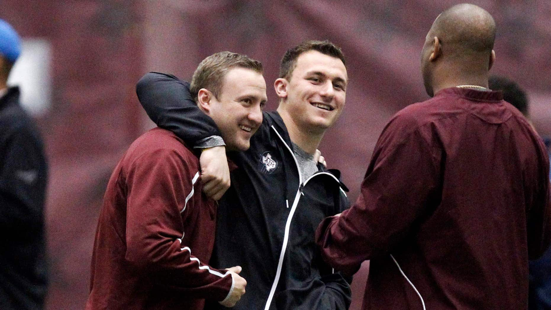FILE - In this March 5, 2014, file photo, Texas A&M quarterback Johnny Manziel, middle, gives offensive coordinator Jake Spavital a hug during Texas A&M pro day in College Station, Texas.
