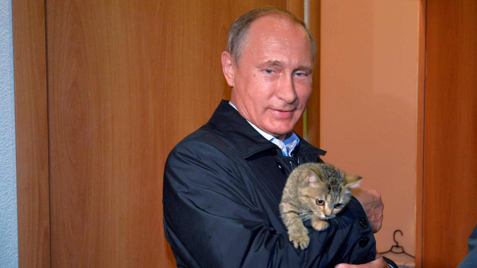 Sept. 4, 2015: Russian President Vladimir Putin holds a cat as he inspects housing built for victims of wildfires in the village of Krasnopolye, in Khakassia, a region in southeastern Siberia, Russia.