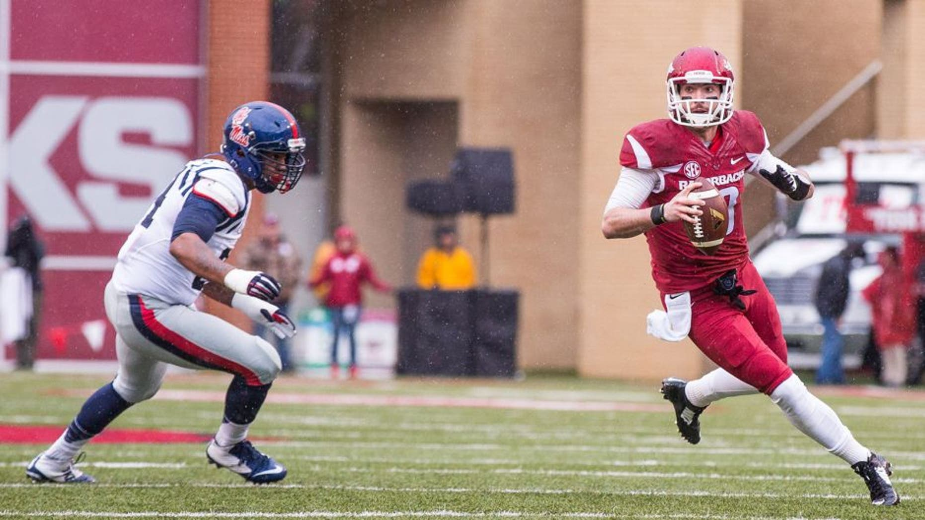 Nov 22, 2014; Fayetteville, AR, USA; Arkansas Razorbacks quarterback Brandon Allen (10) looks to pass while pursued by Ole Miss Rebels defensive tackle Issac Gross (94) during a game at Donald W. Reynolds Razorback Stadium. Arkansas defeated Ole Miss 30-0. Mandatory Credit: Beth Hall-USA TODAY Sports