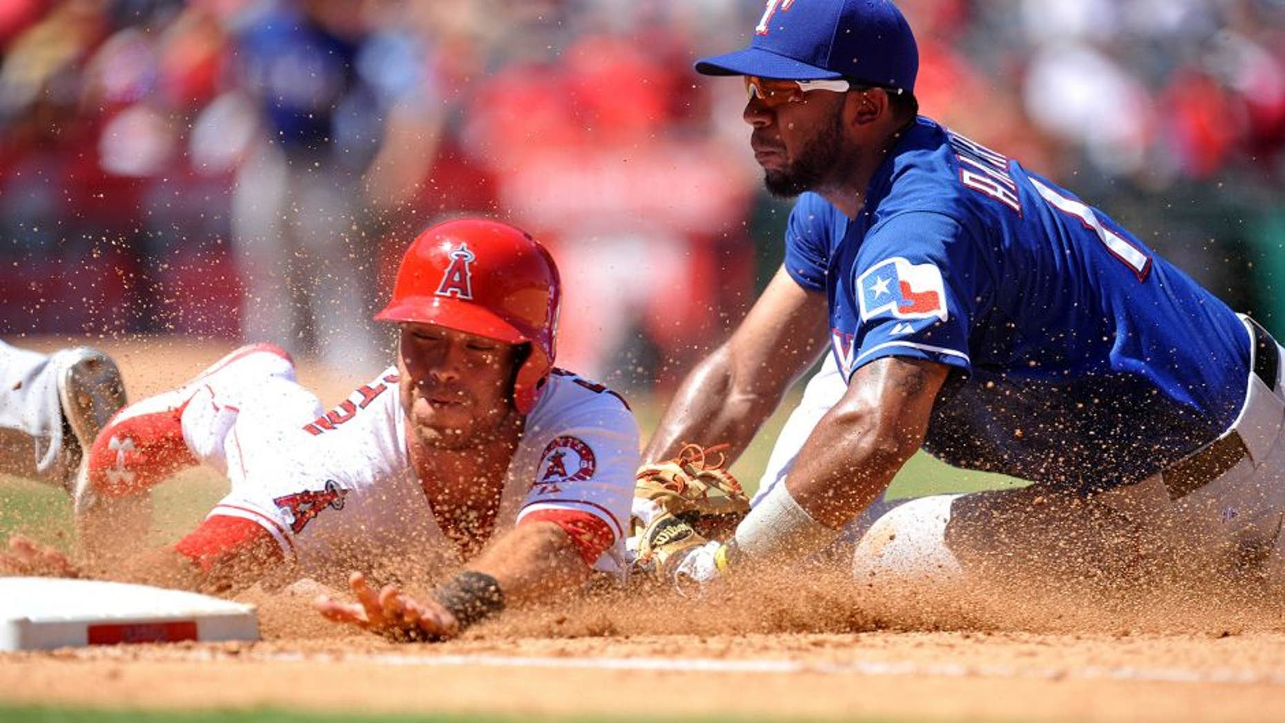 September 6, 2015; Anaheim, CA, USA; Los Angeles Angels third baseman Taylor Featherston (8) is tagged out at first after trying to steal second against Texas Rangers shortstop Elvis Andrus (1) in the fourth inning at Angel Stadium of Anaheim. Mandatory Credit: Gary A. Vasquez-USA TODAY Sports