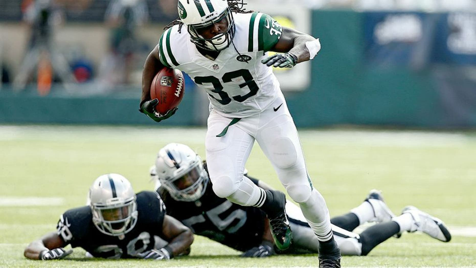 EAST RUTHERFORD, NJ - SEPTEMBER 07: Chris Ivory #33 of the New York Jets rushes after evading tackle attempts by T.J. Carrie #38 and Sio Moore #55 of the Oakland Raiders during the third quarter of a game at MetLife Stadium on September 7, 2014 in East Rutherford, New Jersey. (Photo by Jeff Zelevansky/Getty Images)