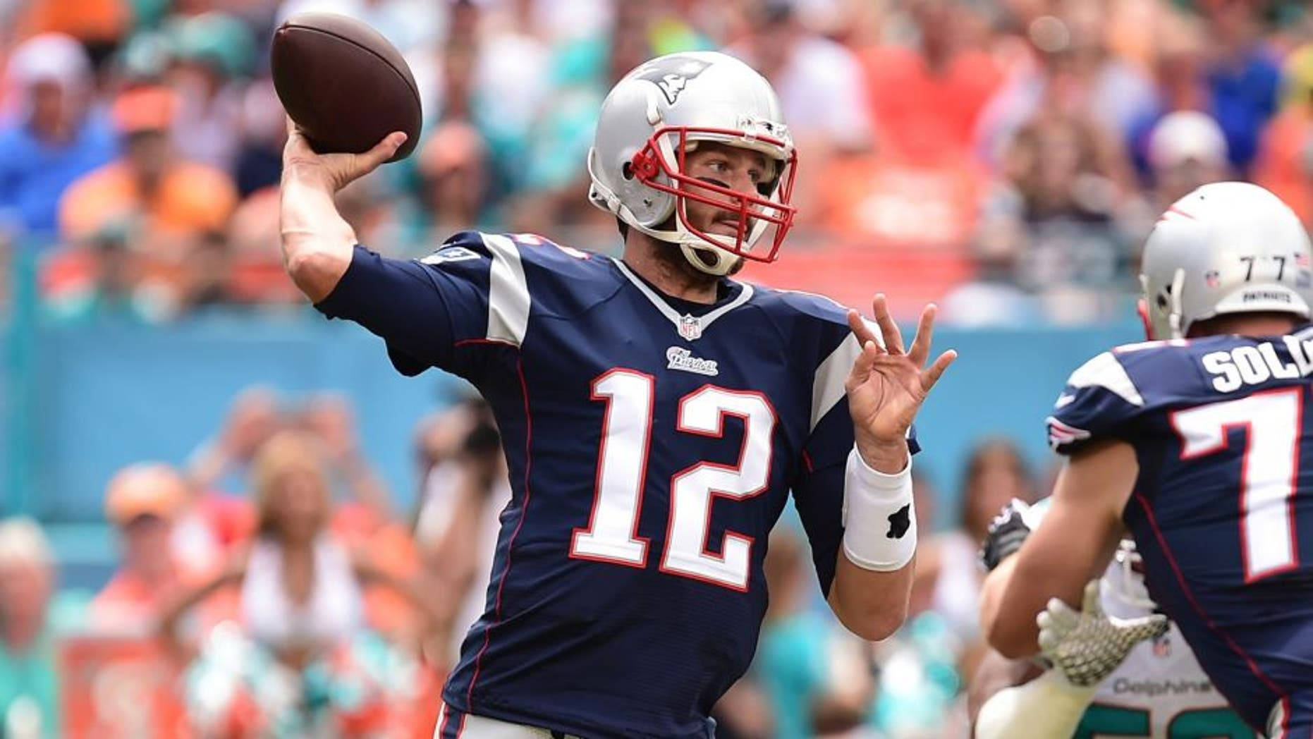 Sep 7, 2014; Miami Gardens, FL, USA; New England Patriots quarterback Tom Brady (12) drops back to pass in the first quarter against the Miami Dolphins at Sun Life Stadium. Mandatory Credit: Brad Barr-USA TODAY Sports
