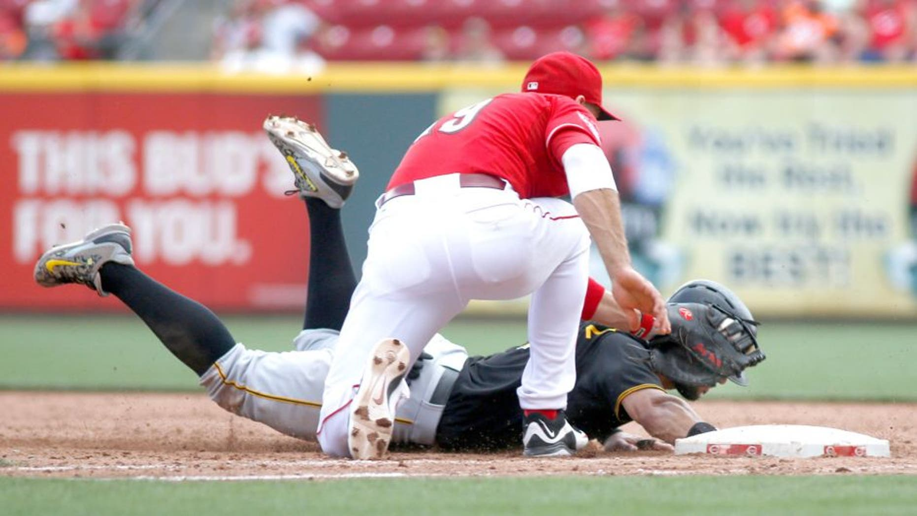 Sep 7, 2015; Cincinnati, OH, USA; Pittsburgh Pirates first baseman Sean Rodriguez (3) is picked off at first by Cincinnati Reds first baseman Joey Votto (19) in the ninth inning at Great American Ball Park. The Reds won 3-1. Mandatory Credit: David Kohl-USA TODAY Sports