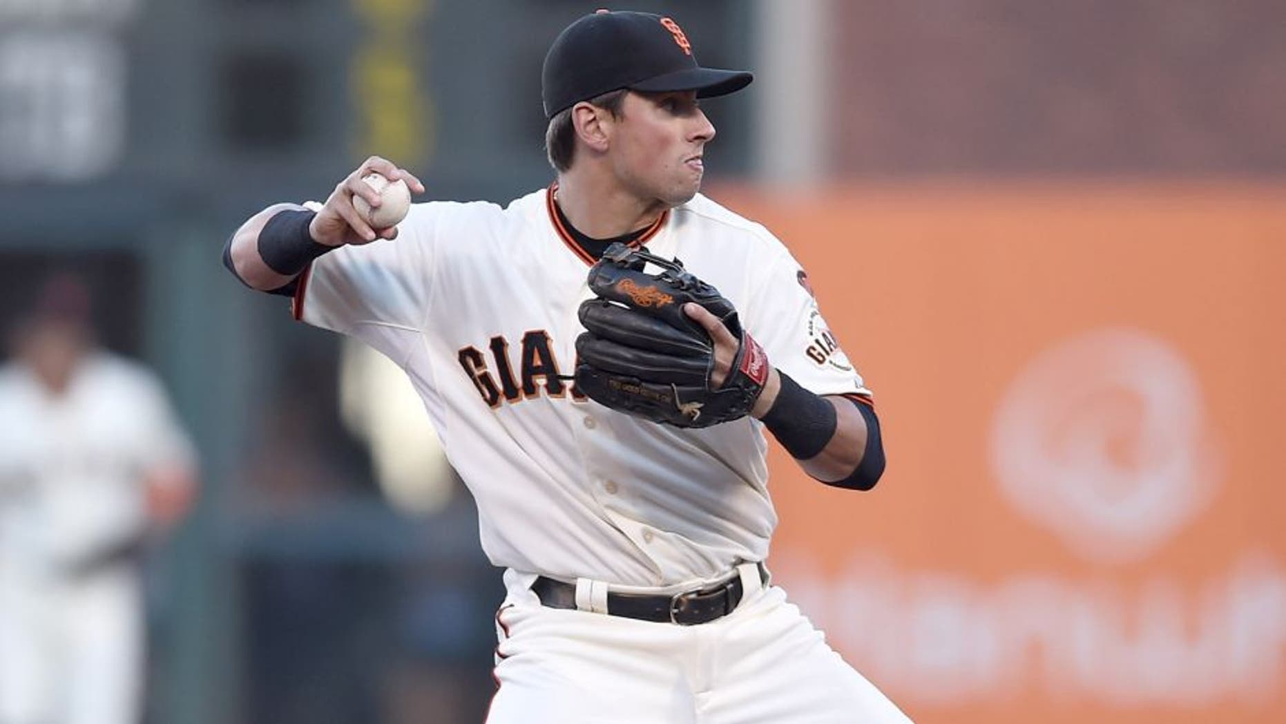 SAN FRANCISCO, CA - JULY 27: Joe Panik #12 of the San Francisco Giants looks to throw to first base and complete the double-play against the Milwaukee Brewers in the top of the first inning at AT&T Park on July 27, 2015 in San Francisco, California. (Photo by Thearon W. Henderson/Getty Images)