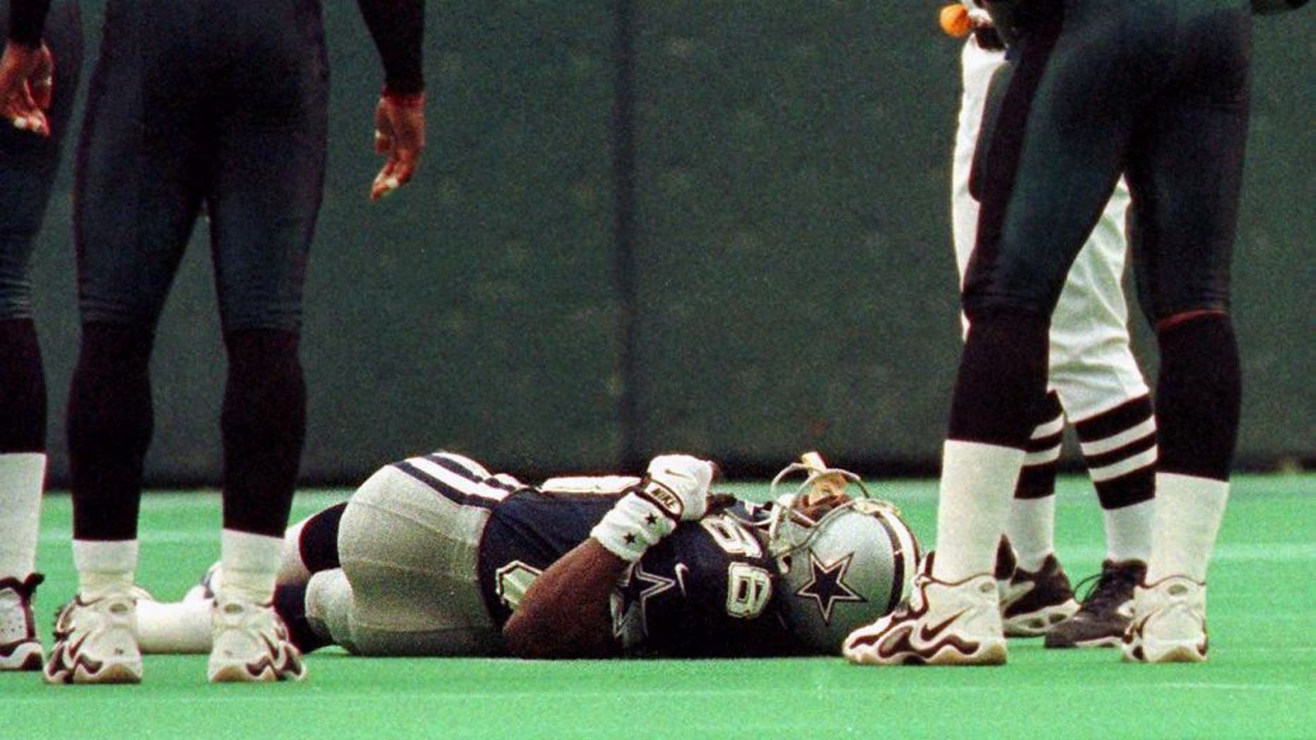 PHILADELPHIA, : Dallas Cowboys player Michael Irvin (C)is on the ground after being injured on a pass play in the first quarter of their game against the Philadelphia Eagles 10 October 1999 in Philadelphia. Standing near Irvin are Eagles players Brian Dawkins (L) and William Thomas (R). Irvin was taken out of the game and to a local hospital for evaluation. The Eagles won 13-10. AFP PHOTO/ TOM MIHALEK (Photo credit should read TOM MIHALEK/AFP/Getty Images)