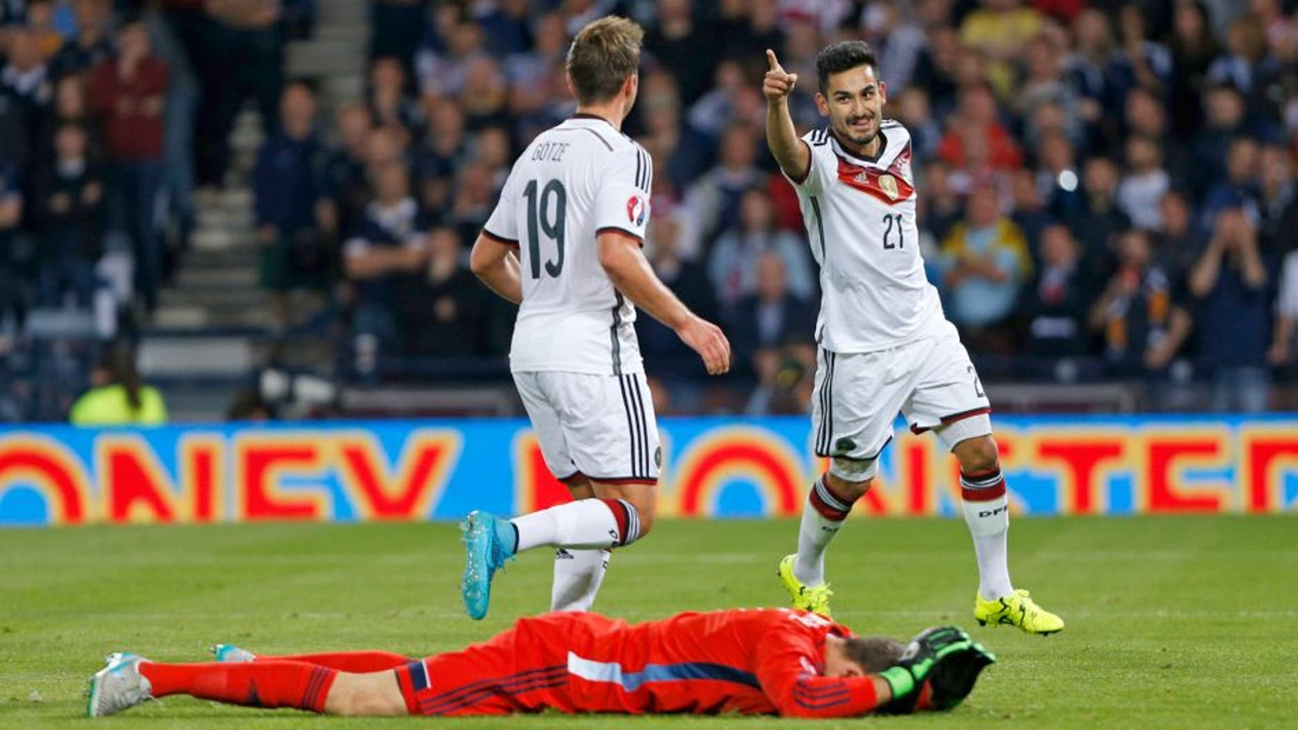 Football - Scotland v Germany - UEFA Euro 2016 Qualifying Group D - Hampden Park, Glasgow, Scotland - 7/9/15 Ilkay Gundogan celebrates with team mates after scoring the third goal for Germany as Scotland's David Marshall looks dejected Reuters / Russell Cheyne Livepic EDITORIAL USE ONLY.