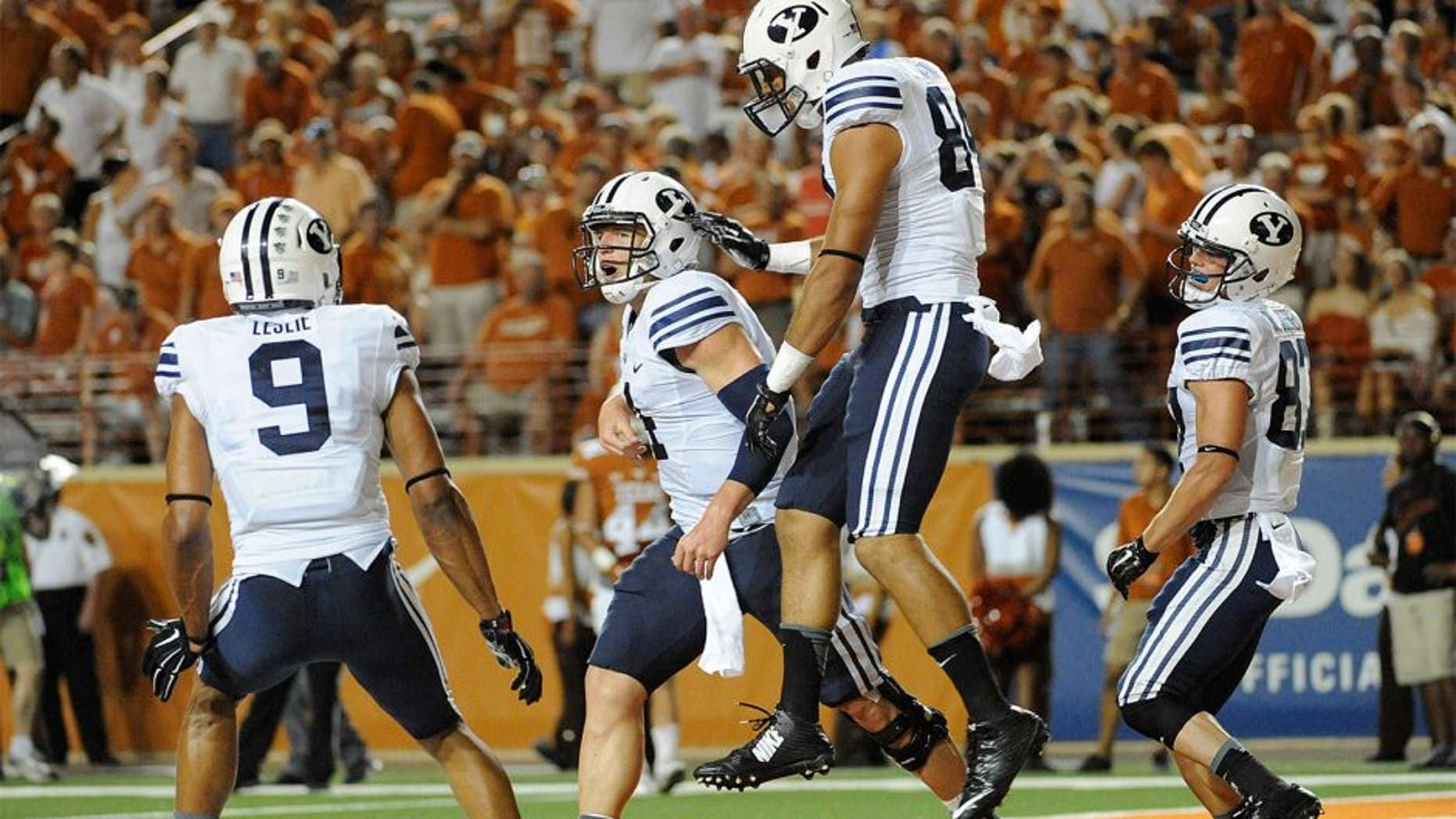 Sep 6, 2014; Austin, TX, USA; Brigham Young Cougars quarterback Taysom Hill (4) and tight end Devin Mahina (84) and wide receivers Jordan Leslie (9) and Mitchell Juergens (87) react after a touchdown against the Texas Longhorns during the second half at Darrell K Royal-Texas Memorial Stadium. BYU beat Texas 41-7. Mandatory Credit: Brendan Maloney-USA TODAY Sports