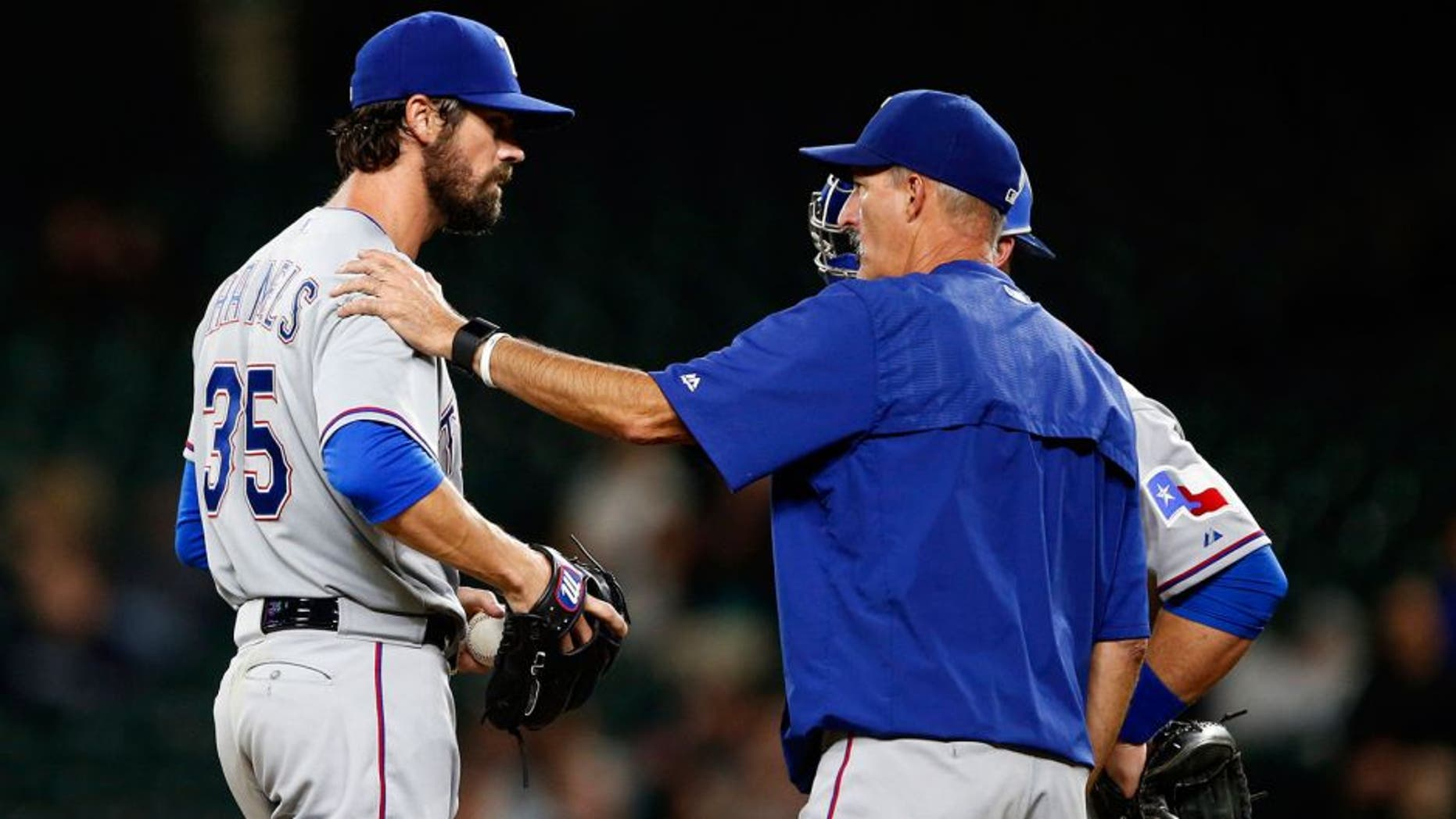 Sep 8, 2015; Seattle, WA, USA; Texas Rangers pitching coach Mike Maddux (31) talks with pitcher Cole Hamels (35) during the seventh inning against the Seattle Mariners at Safeco Field. Mandatory Credit: Joe Nicholson-USA TODAY Sports