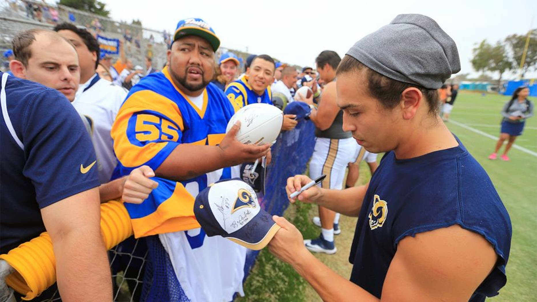 OXNARD, CALIF. -- MONDAY, AUGUST 17, 2015: St. Louis Rams wide receiver and U.S. Army veteran Daniel Rodriguez signs autographs for hopeful Los Angeles Rams fans following the St. Louis Rams-Dallas Cowboys NFL scrimmage at training camp in Oxnard Monday, Aug. 17, 2015. The Dallas Cowboys scrimmaged against the St. Louis Rams. The Rams are making an appearance in Southern California now that they're trying to possibly move back. Photo taken in Oxnard, Calif., on Aug. 17, 2015. (Allen J. Schaben / Los Angeles Times)