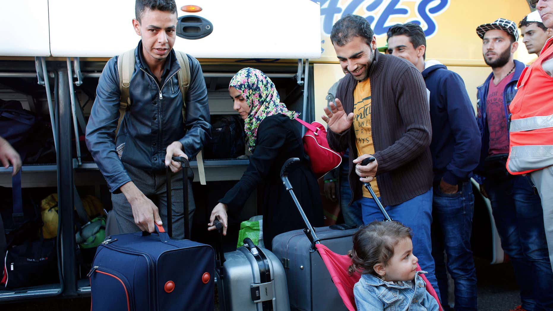 Sept. 9, 2015: Wissam Ahmed, from Iraq, left, and other refugees arrive after an overnight bus trip from Germany, in Champagne-sur-Seine, south of Paris, France.