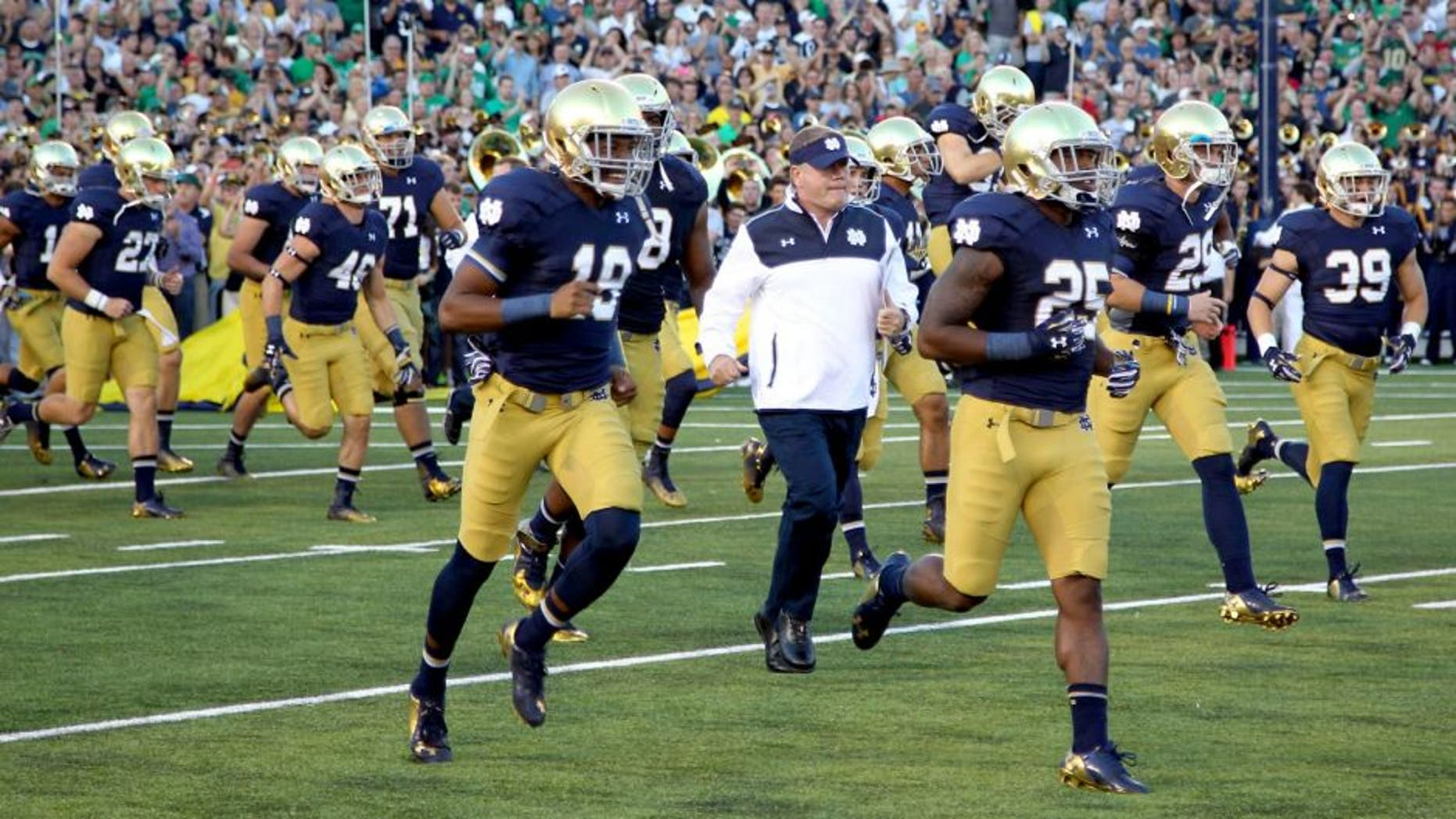 Sep 6, 2014; South Bend, IN, USA; Notre Dame Fighting Irish coach Brian Kelly runs onto the field with the team before the game against the Michigan Wolverines at Notre Dame Stadium. Mandatory Credit: Brian Spurlock-USA TODAY Sports