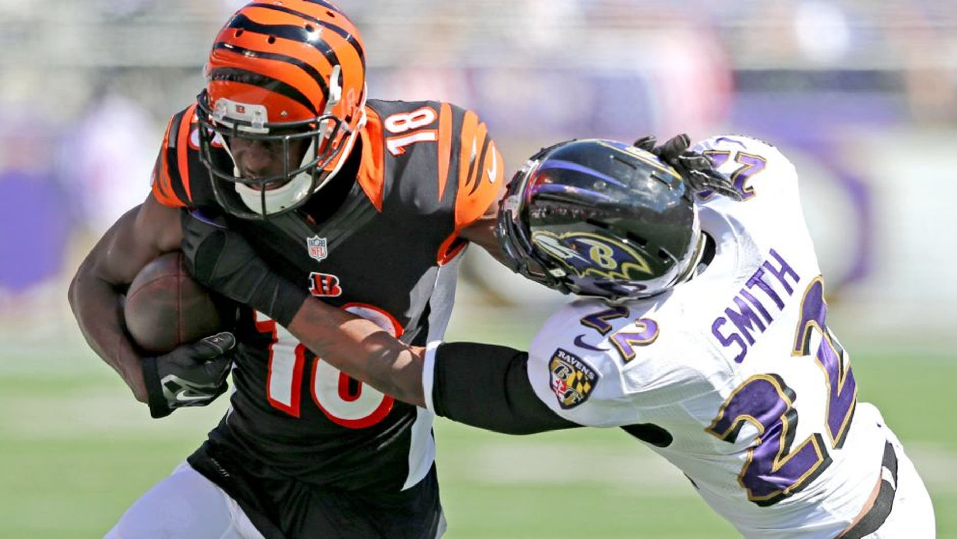 Sep 7, 2014; Baltimore, MD, USA; Cincinnati Bengals wide receiver A.J. Green (18) is tackled after a catch by Baltimore Ravens cornerback Jimmy Smith (22) at M&T Bank Stadium. Mandatory Credit: Mitch Stringer-USA TODAY Sports
