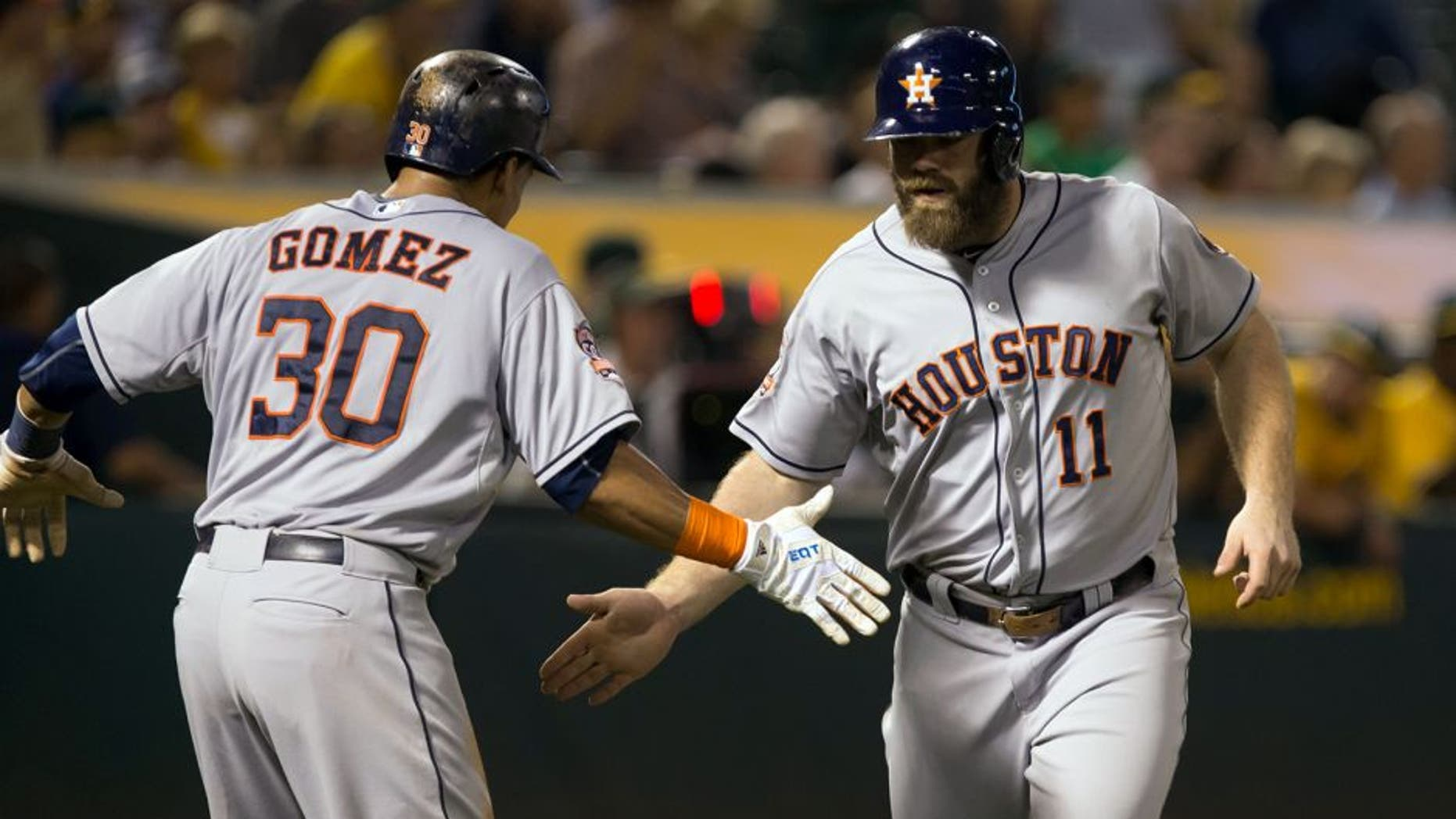 Sep 9, 2015; Oakland, CA, USA; Houston Astros designated hitter Evan Gattis (11) high fives center fielder Carlos Gomez (30) after batting him in on a two run home run against the Oakland Athletics during the fifth inning at O.co Coliseum. Mandatory Credit: Kelley L Cox-USA TODAY Sports