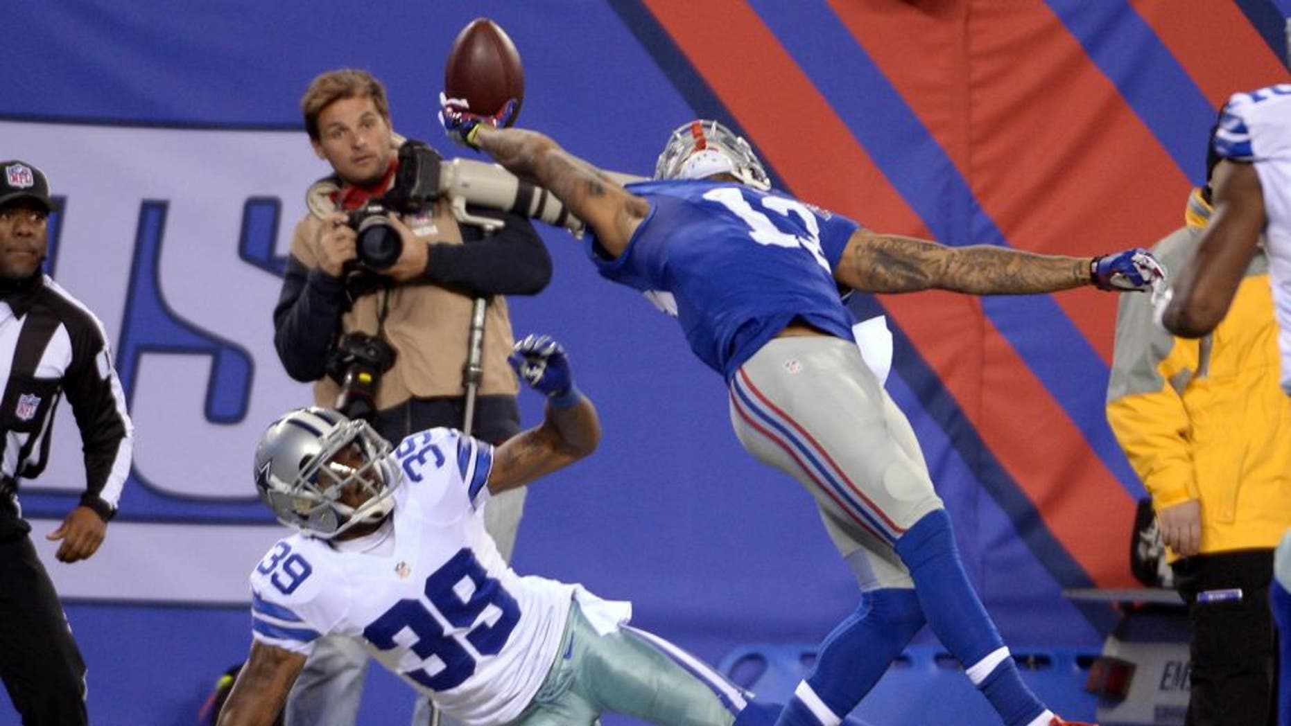 Nov 23, 2014; East Rutherford, NJ, USA; New York Giants wide receiver Odell Beckham (13) catches a one handed touchdown against by Dallas Cowboys cornerback Brandon Carr (39) during the second quarter at MetLife Stadium. Mandatory Credit: Robert Deutsch-USA TODAY Sports