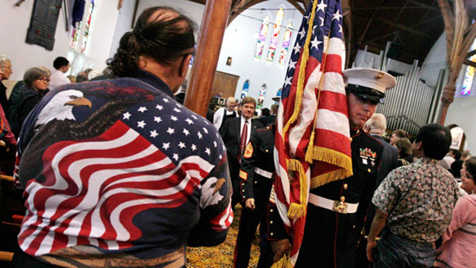 Sept. 11: A member of the U.S. Marines carries their national flag past a man wearing a stars and stripes shirt during a special service to commemorate the 10th anniversary of the Sept. 11 terrorist attacks, at a church in New Plymouth, New Zealand.