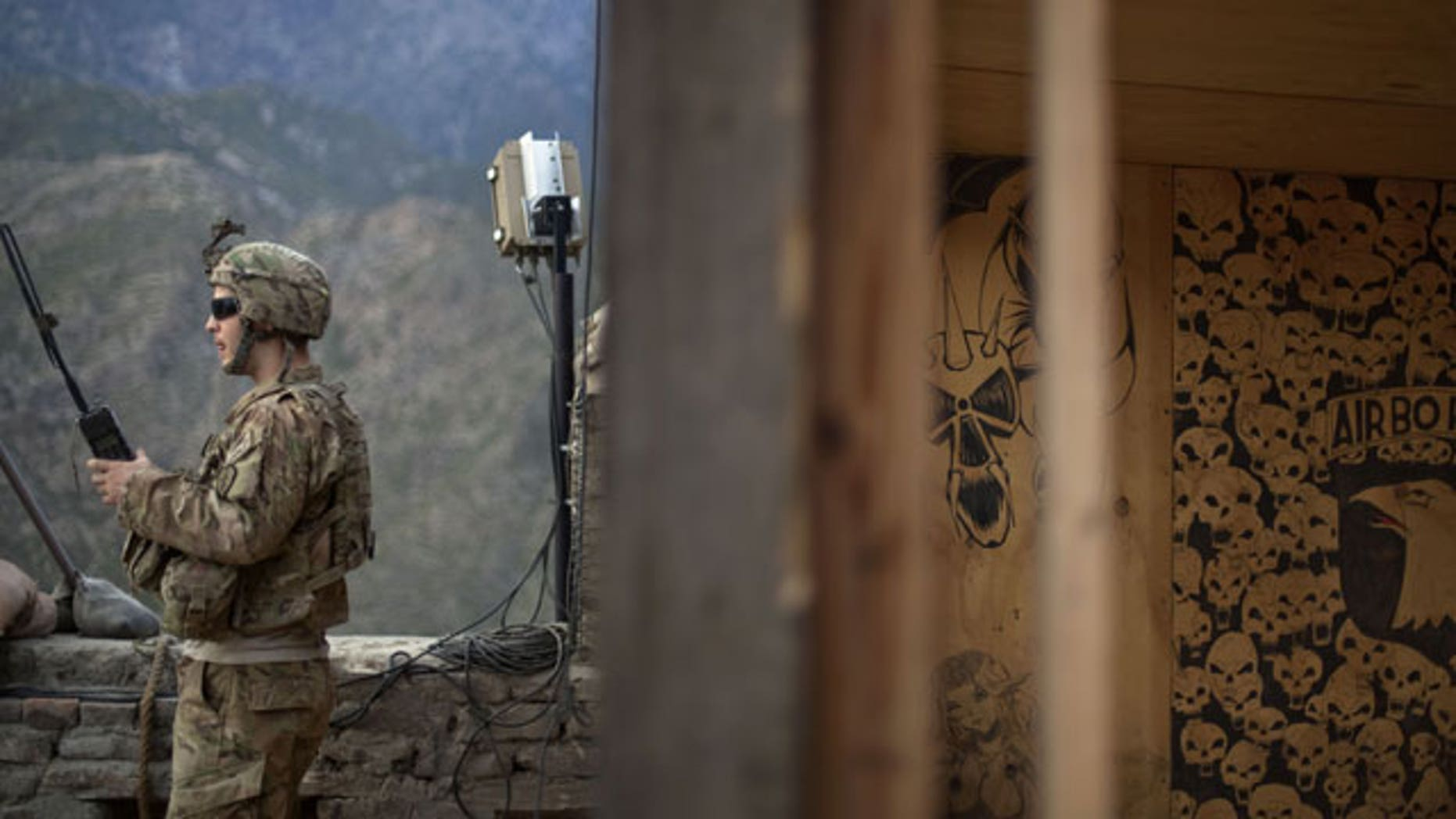 Sgt. Matt Murray, 25, of Warwick, RI., with the U.S. Army's Bravo Company of the 25th Infantry Division, 3rd Brigade Combat Team, 2nd Battalion 27th Infantry Regiment based in Schofield Barracks, Hawaii, listens to the radio next to graffiti left by a previous unit after receiving reports of an impending attack by insurgents Friday, Sept. 9, 2011 at Observation Post Coleman in Kunar province, Afghanistan.