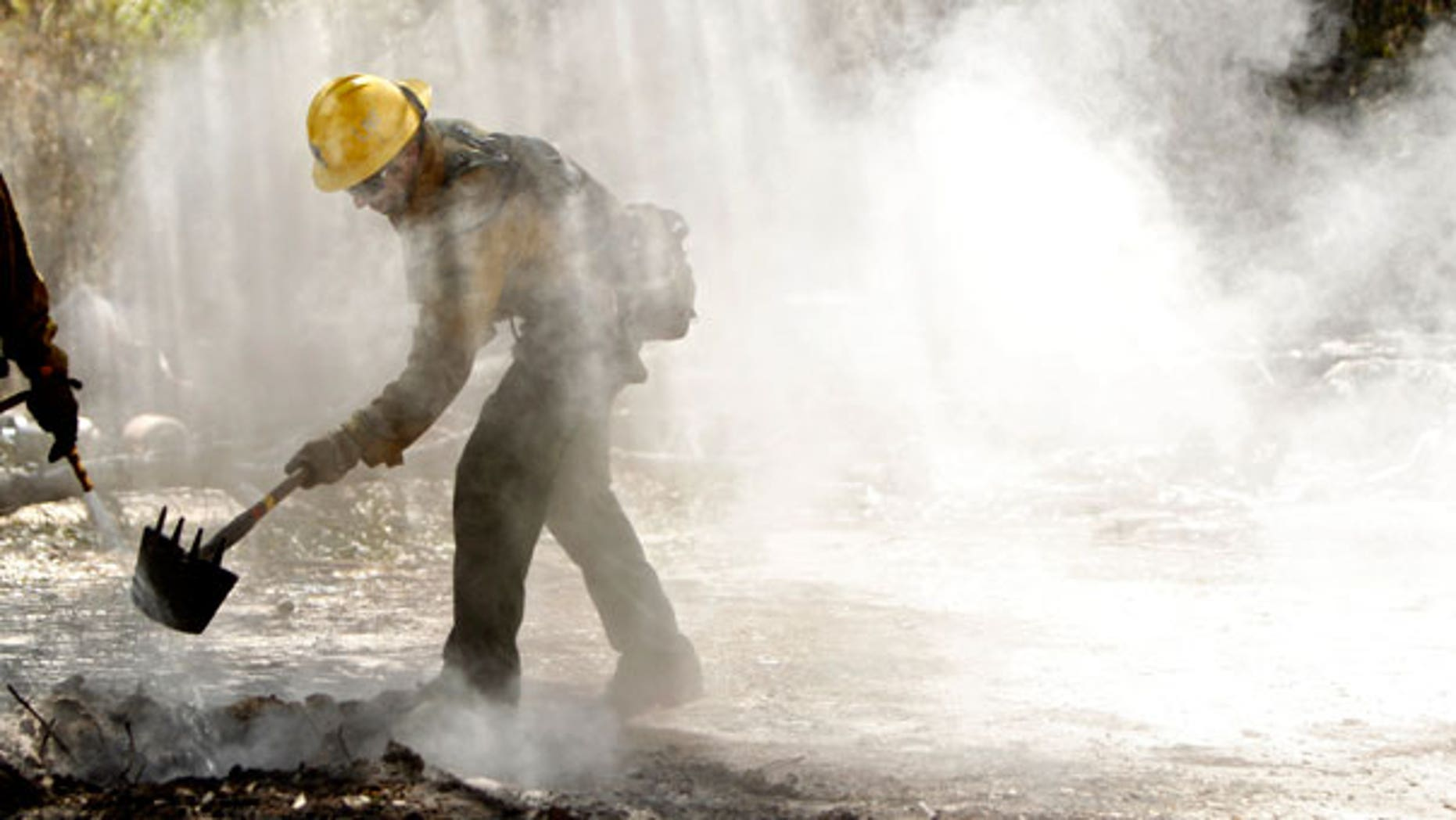 Sept. 10: Tommy Ratto, a fire fighter from the Lassen National Forest in Calif., team cleans up a hot spot after the destructive wildfire in Bastrop, Texas.