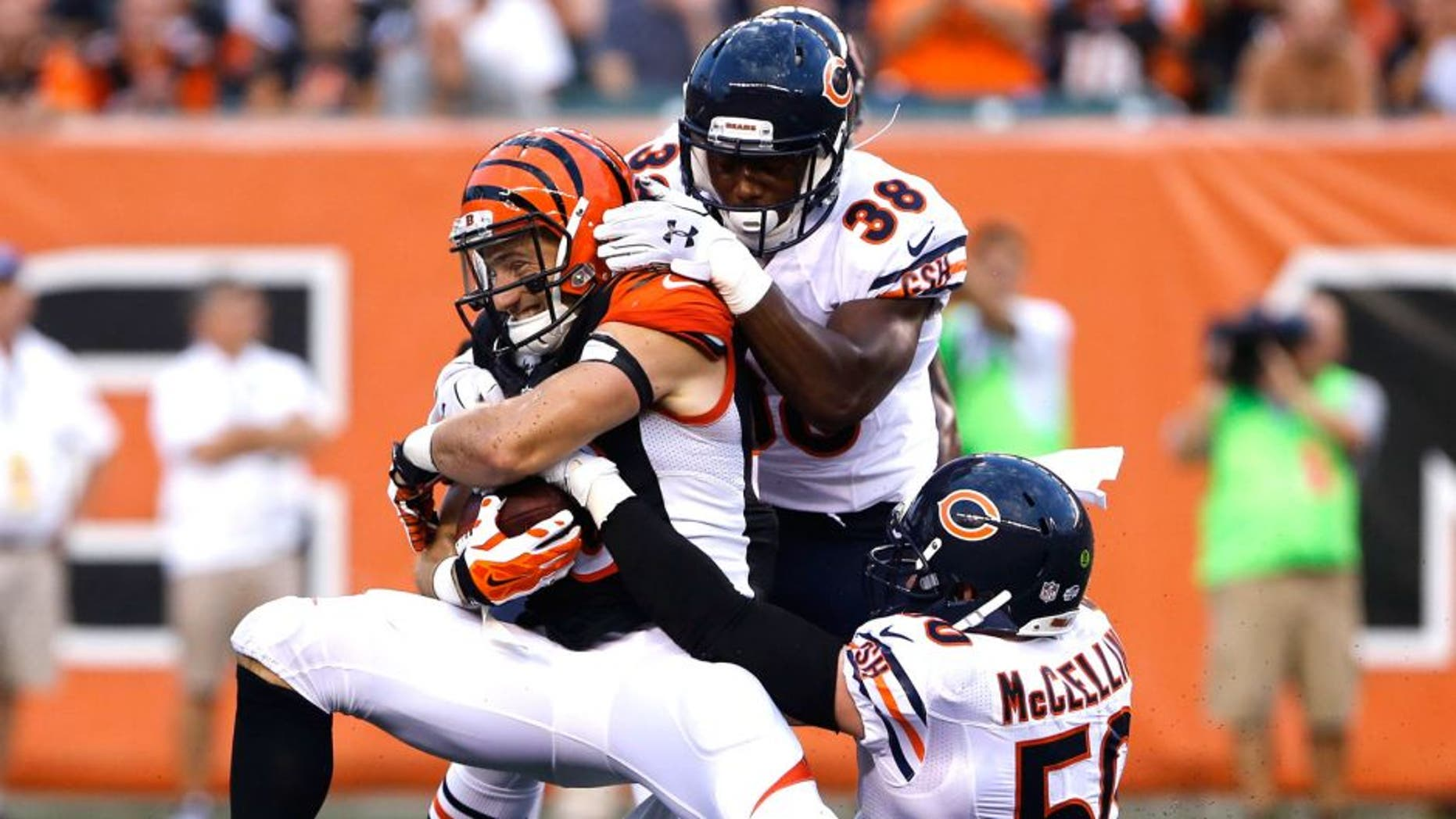 Aug 29, 2015; Cincinnati, OH, USA; Cincinnati Bengals running back Rex Burkhead (33) is tackled by Chicago Bears free safety Adrian Amos (38) and outside linebacker Shea McClellin (50) after making a catch in the first half in a preseason NFL football game at Paul Brown Stadium. Mandatory Credit: Aaron Doster-USA TODAY Sports