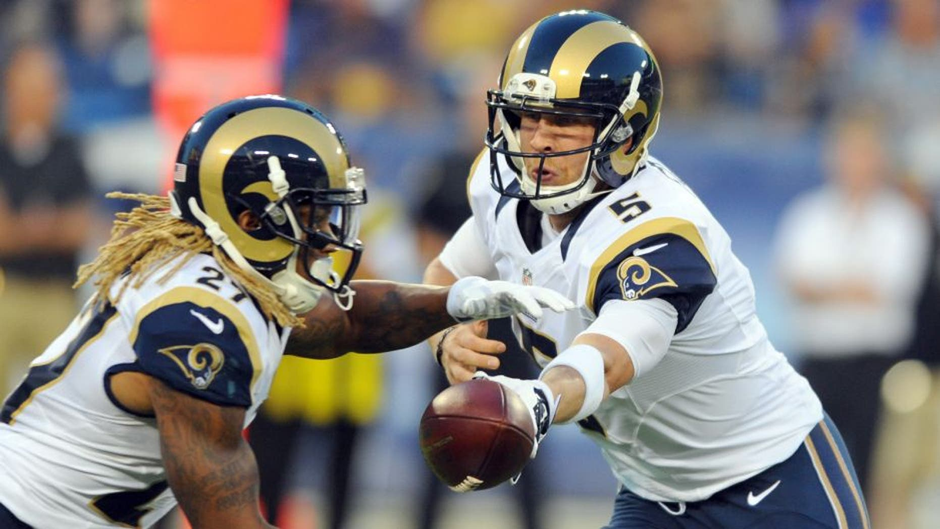 Aug 23, 2015; Nashville, TN, USA; St. Louis Rams quarterback Nick Foles (5) hands the ball off to running back Tre Mason (27) during the first half against the Tennessee Titans at Nissan Stadium. Mandatory Credit: Christopher Hanewinckel-USA TODAY Sports