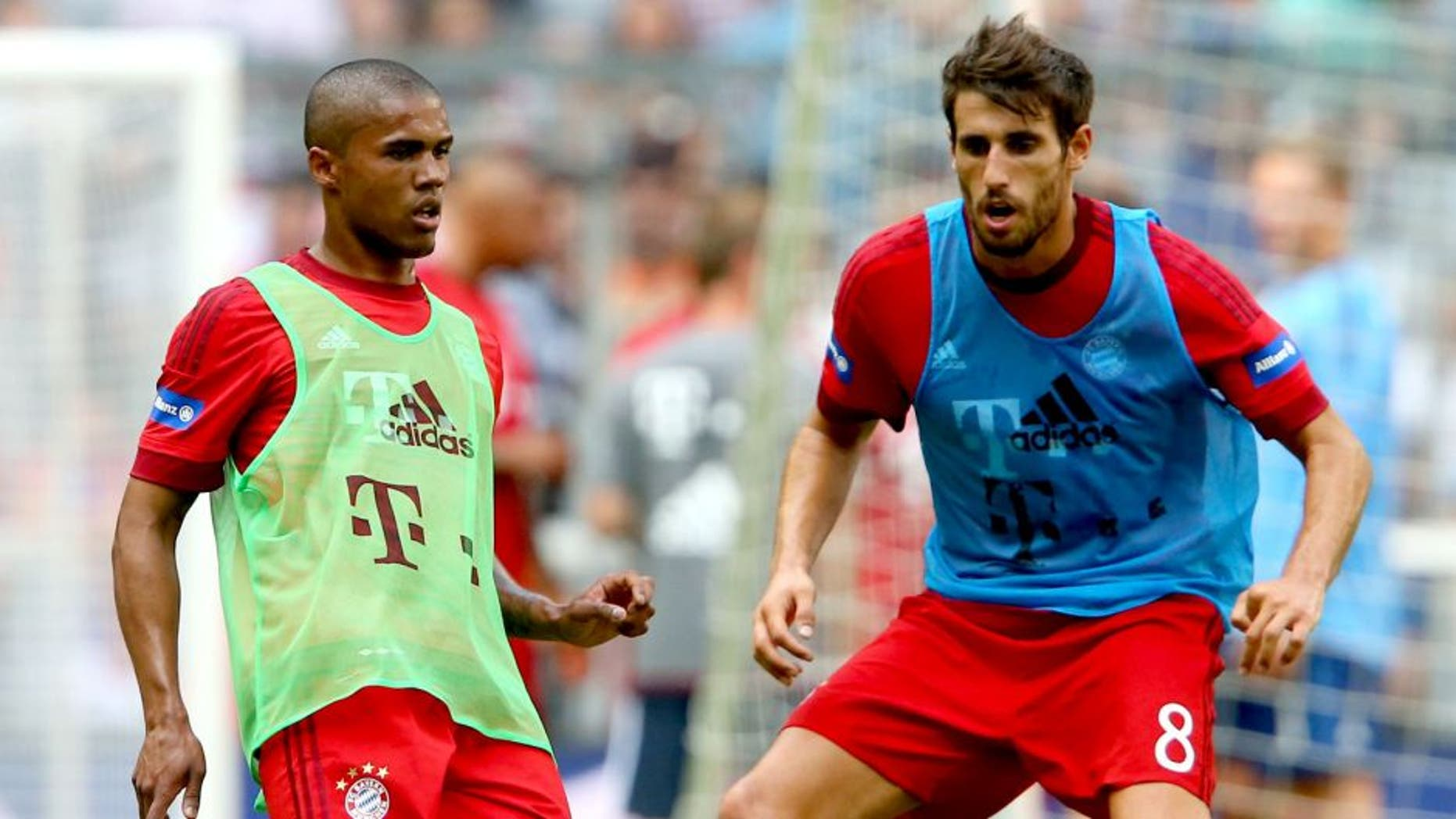 MUNICH, GERMANY - JULY 11: Douglas Costa (L) battles for the ball with Javier Martinez during a training session after the FC Bayern Muenchen season opening and team presentation at Allianz Arena on July 11, 2015 in Munich, Germany. (Photo by Alexander Hassenstein/Bongarts/Getty Images)