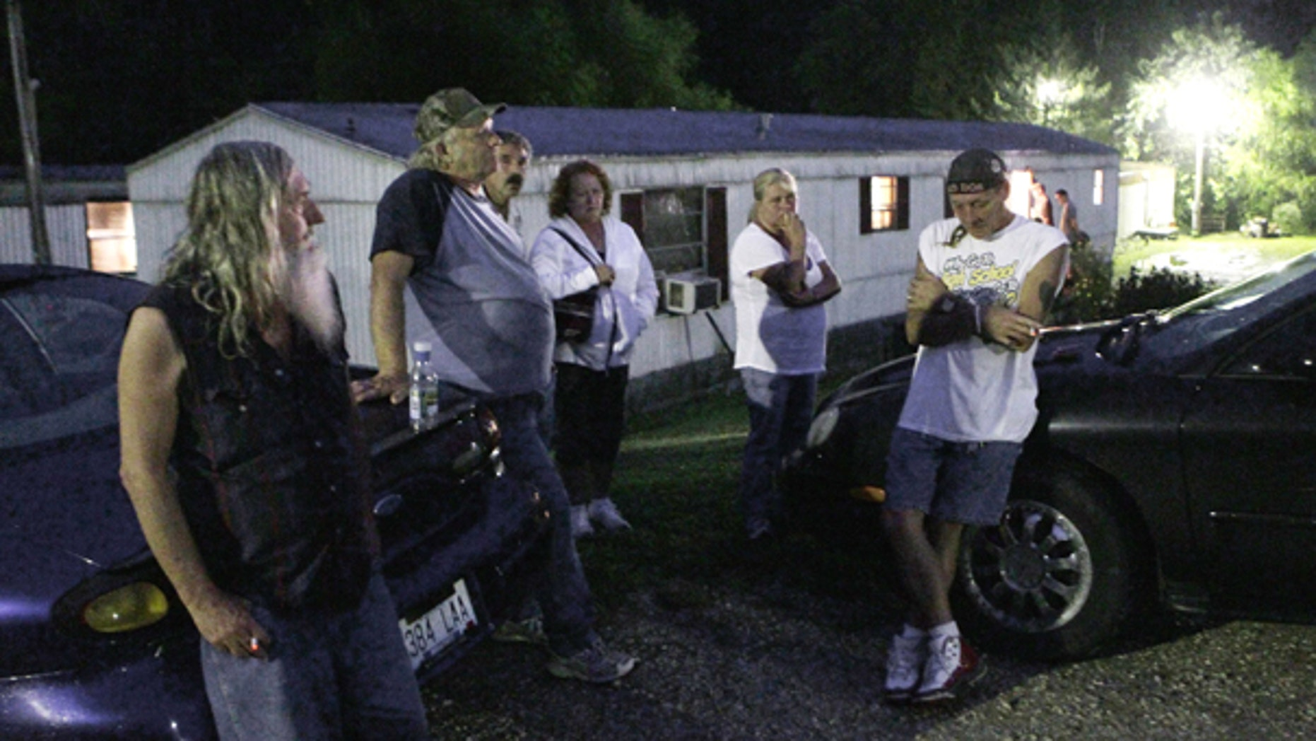Sept. 11: Friends and neighbors gather with J.D. Kilborn, right, outside the trailer where Stanley Neace killed Kilborn's wife Tammy in Jackson, Ky. Neace killed five people before killing himself.