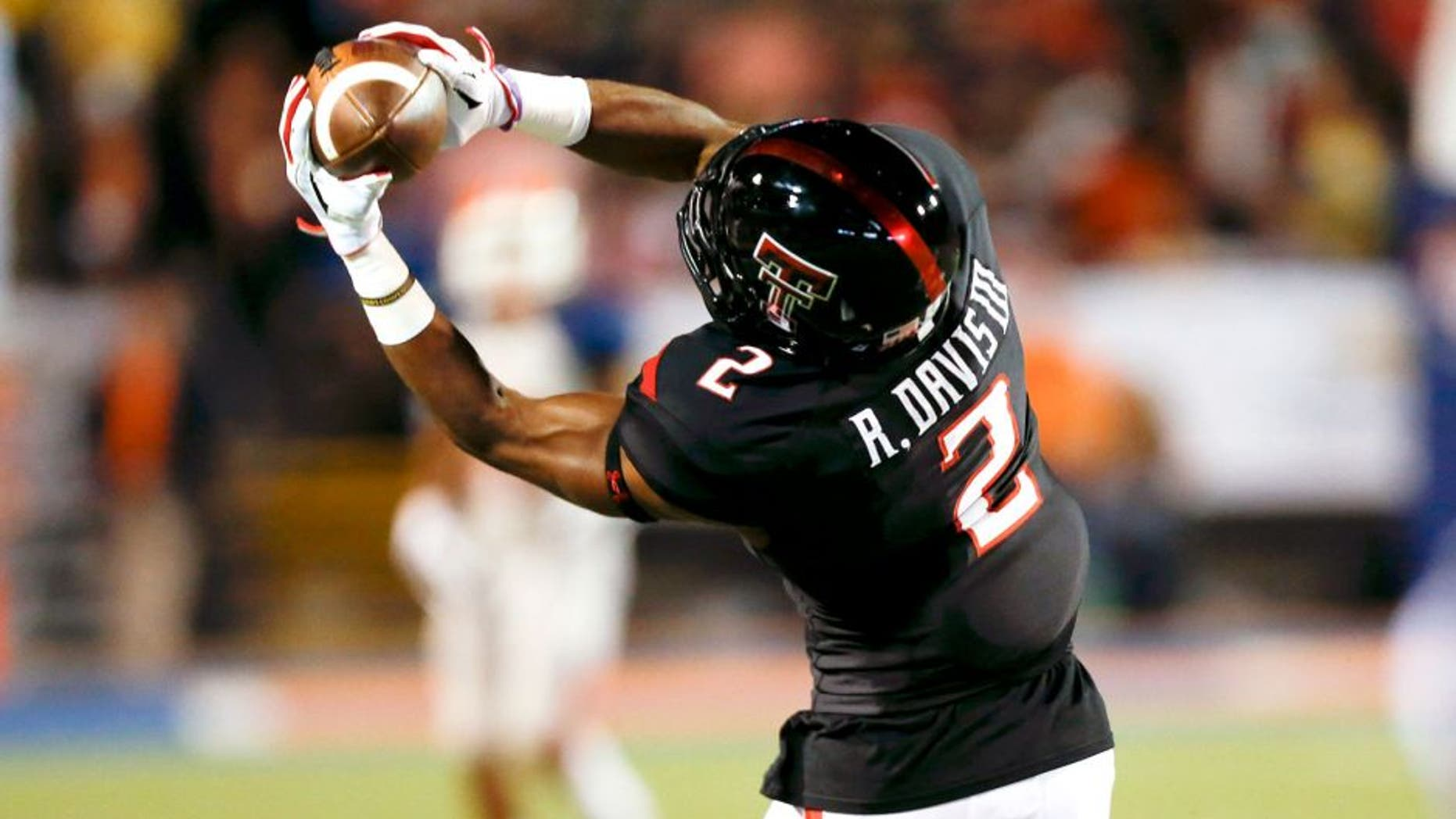 Sep 6, 2014; El Paso, TX, USA; Texas Tech Red Raiders wide receiver Reginald Davis (2) catches a ball against the UTEP Miners defense at Sun Bowl Stadium. Mandatory Credit: Ivan Pierre Aguirre-USA TODAY Sports