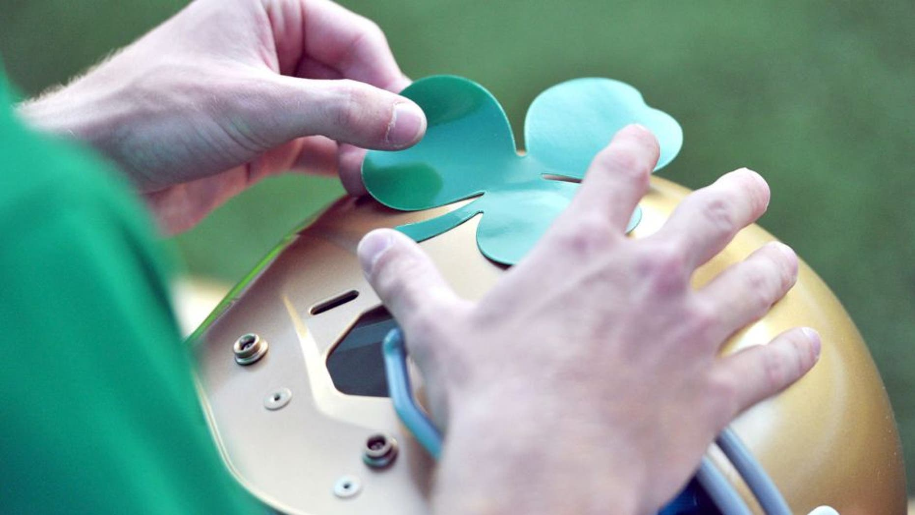 Sept. 10, 2011; Ann Arbor, MI, USA; A student manager applies a shamrock decal to a Notre Dame helmet before the game between the Notre Dame Fighting Irish and the Michigan Wolverines at Michigan Stadium. Mandatory Credit: Matt Cashore-USA TODAY Sports