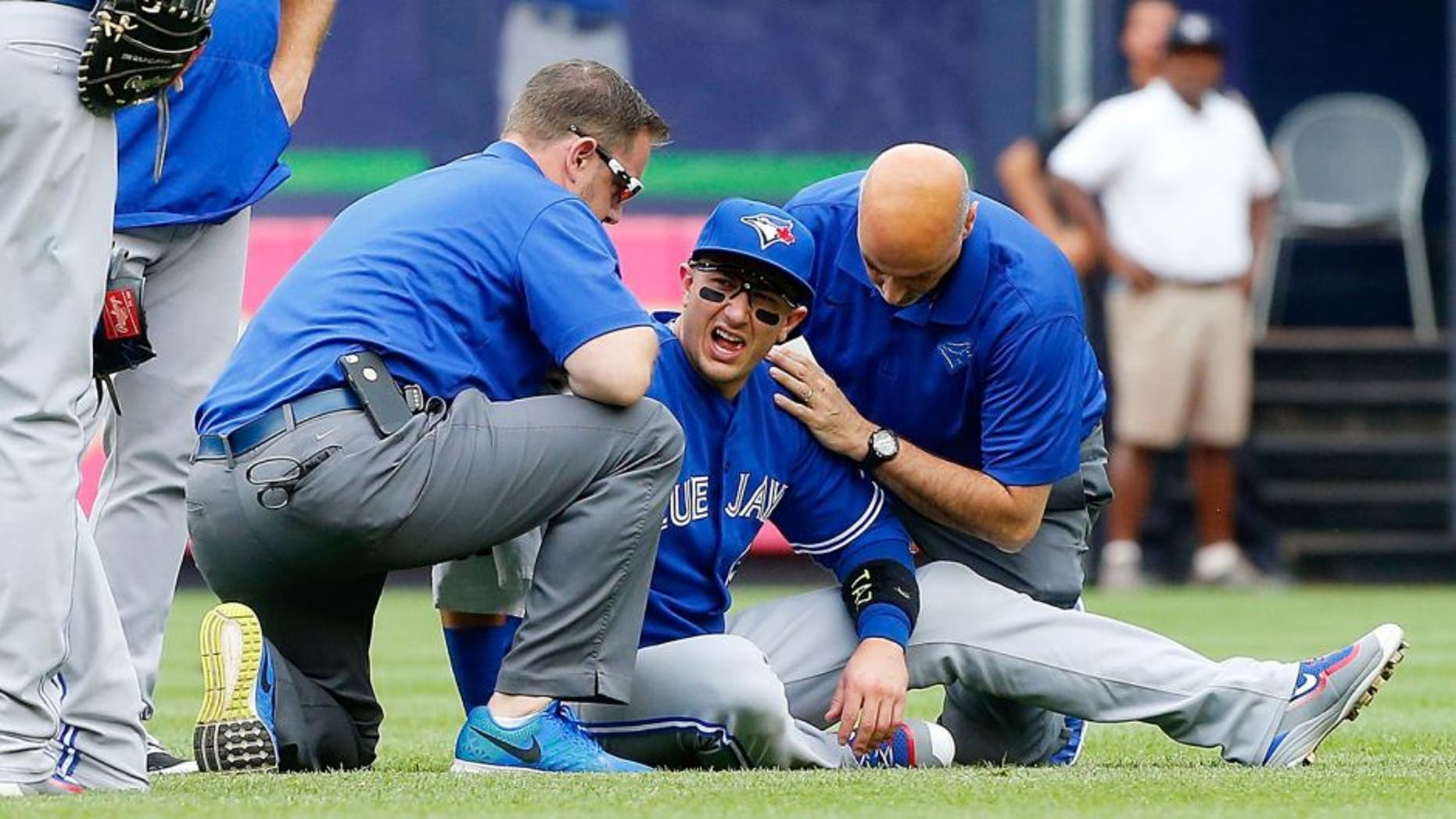 NEW YORK, NY - SEPTEMBER 12: Troy Tulowitzki #2 of the Toronto Blue Jays is tended to by team personnel after colliding with a teammate while making a catch for the final out of the second inning against the New York Yankees at Yankee Stadium on September 12, 2015 in the Bronx borough of New York City. (Photo by Jim McIsaac/Getty Images)