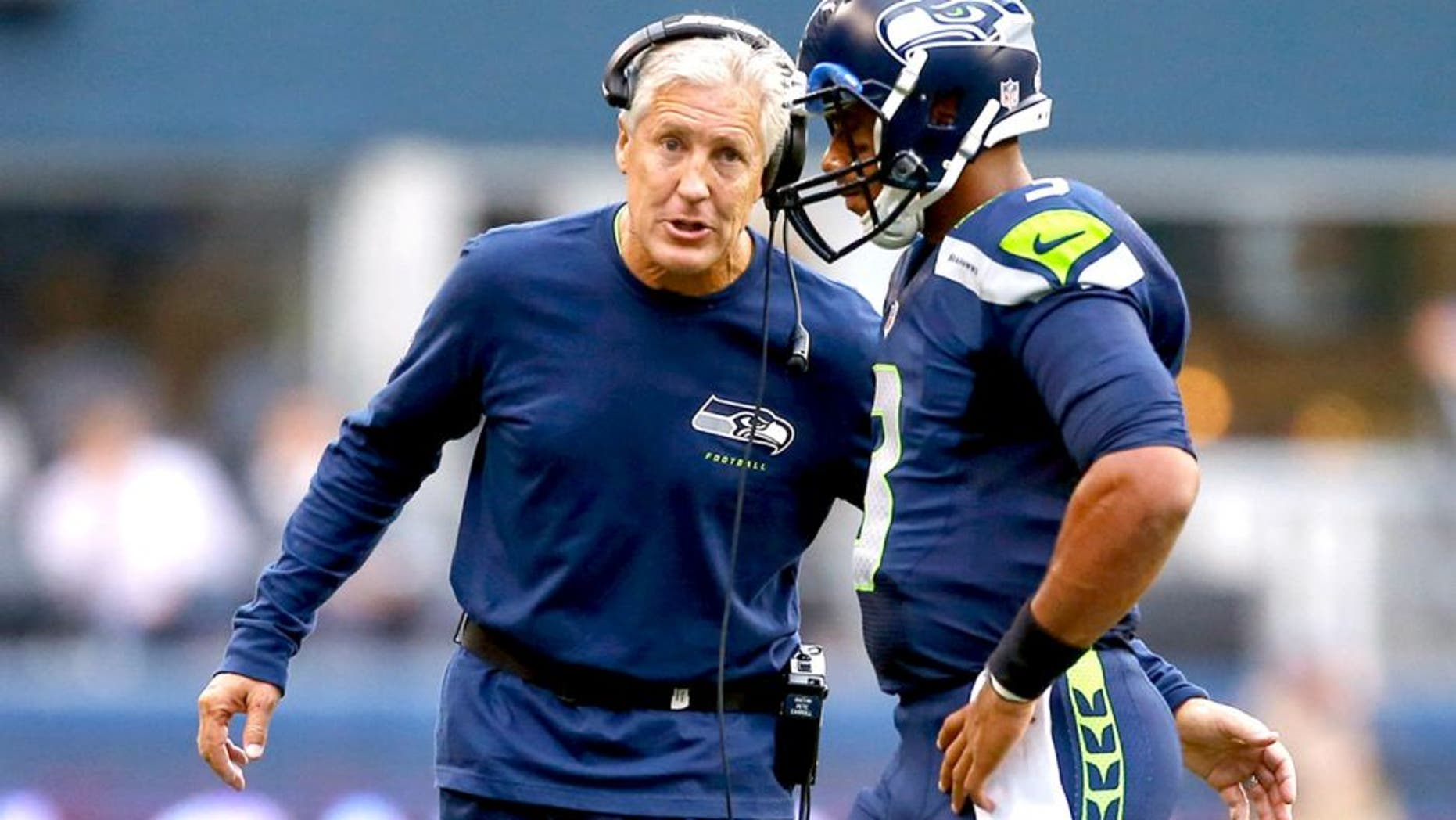 SEATTLE, WA - AUGUST 15: Quarterback Russell Wilson #3 of the Seattle Seahawks talks with head coach Pete Carroll against the San Diego Chargers at CenturyLink Field on August 15, 2014 in Seattle, Washington. (Photo by Otto Greule Jr/Getty Images)
