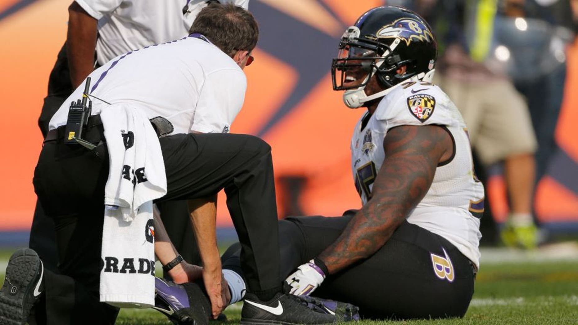 Baltimore Ravens outside linebacker Terrell Suggs is treated on the field during the second half of an NFL football game against the Denver Broncos Sunday, Sept. 13, 2015, in Denver. (AP Photo/Jack Dempsey)