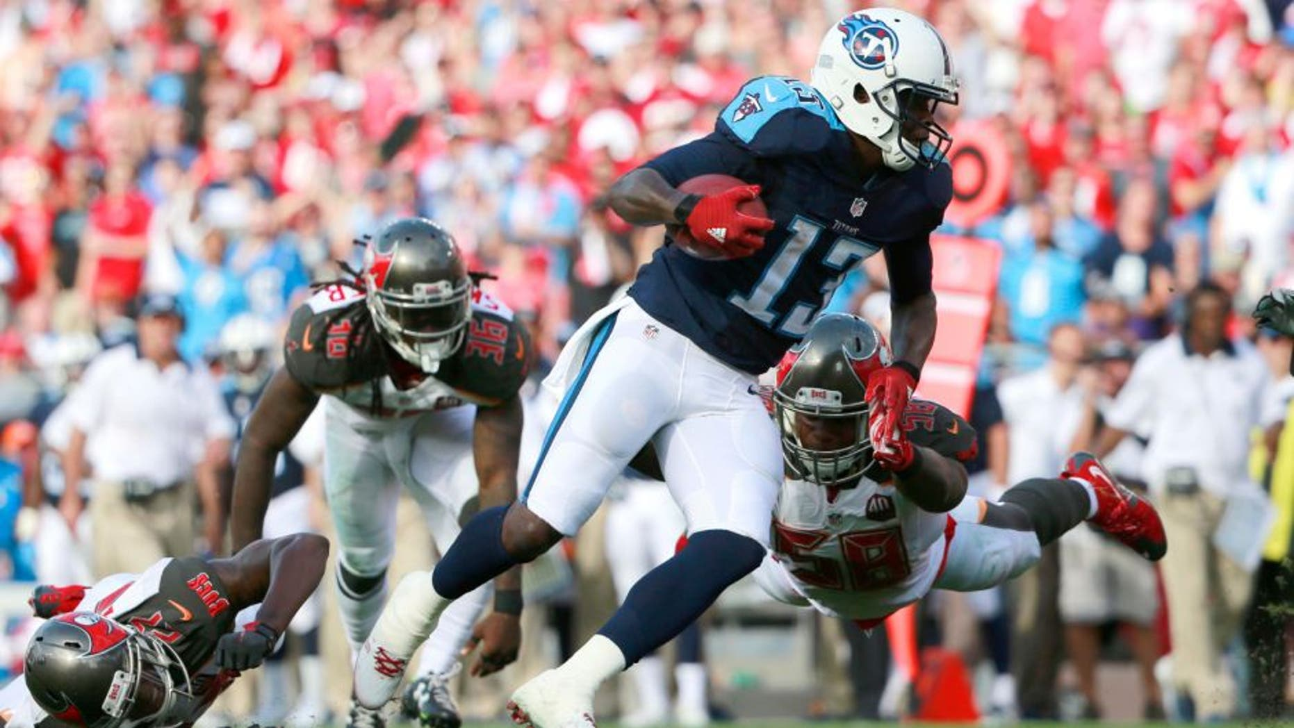 Sep 13, 2015; Tampa, FL, USA; Tennessee Titans wide receiver Kendall Wright (13) runs past Tampa Bay Buccaneers outside linebacker Kwon Alexander (58) during the first half at Raymond James Stadium. Mandatory Credit: Kim Klement-USA TODAY Sports