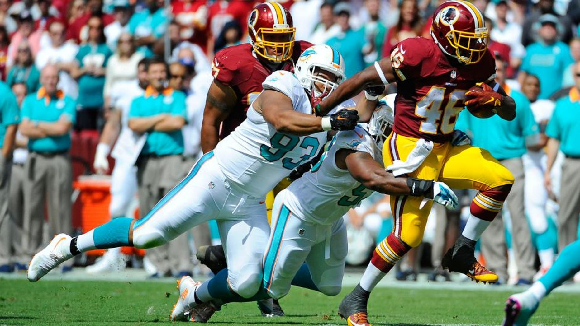 Sep 13, 2015; Landover, MD, USA; Washington Redskins running back Alfred Morris (46) is tackled by Miami Dolphins defensive tackle Ndamukong Suh (93) and outside linebacker Koa Misi (55) during the first half at FedEx Field. Mandatory Credit: Brad Mills-USA TODAY Sports
