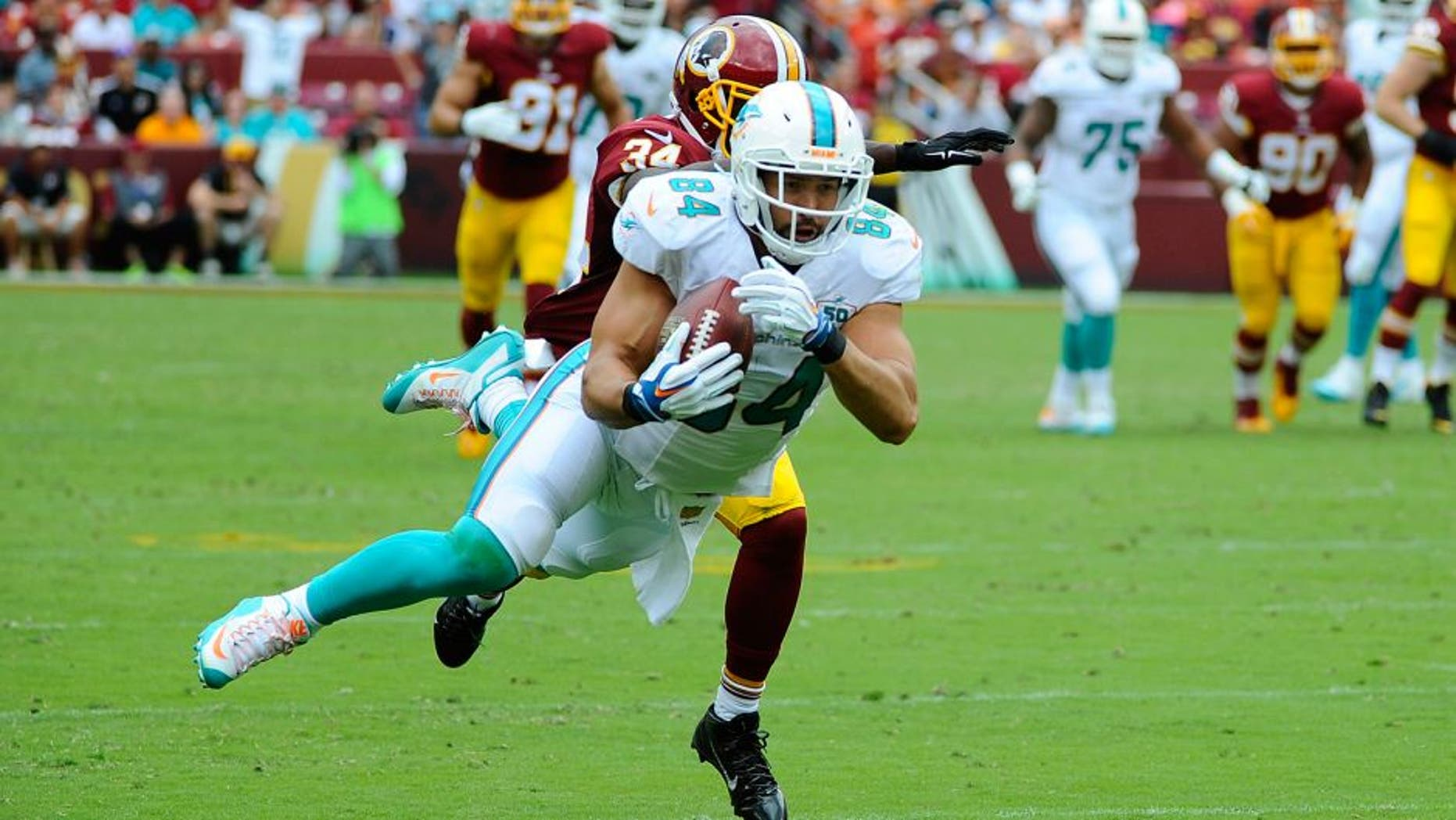 Sep 13, 2015; Landover, MD, USA; Miami Dolphins tight end Jordan Cameron (84) makes a diving catch past Washington Redskins free safety Trenton Robinson (34) during the second half at FedEx Field. Mandatory Credit: Brad Mills-USA TODAY Sports