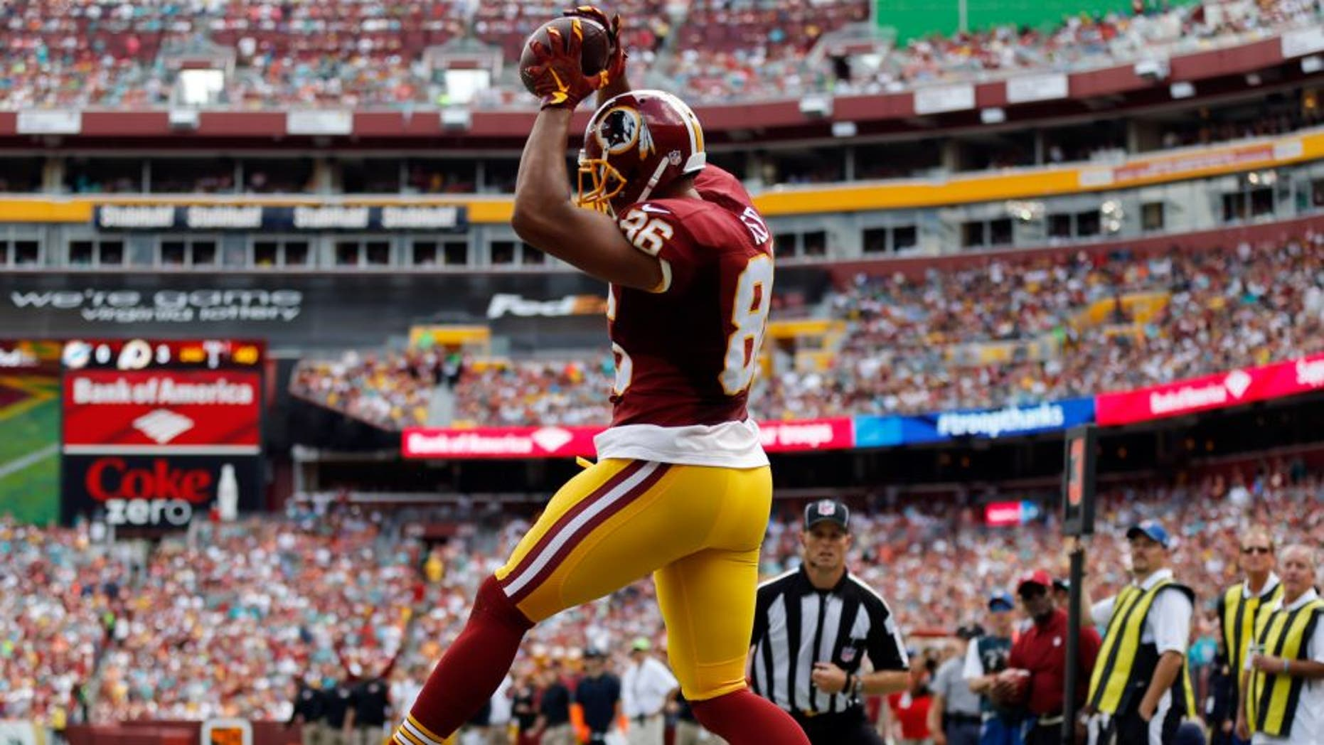 Washington Redskins tight end Jordan Reed (86) catches a touchdown pass over Miami Dolphins strong safety Reshad Jones (20) during the first half of an NFL football game Sunday, Sept. 13, 2015, in Landover, Md. (AP Photo/Patrick Semansky)