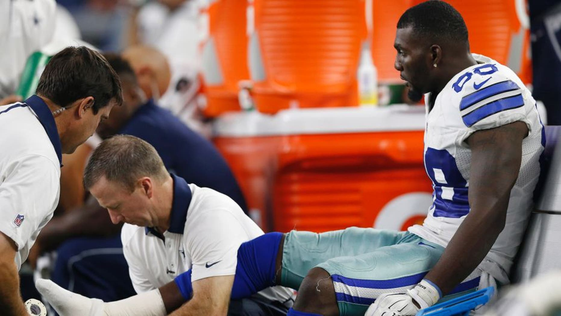 Sep 13, 2015; Arlington, TX, USA; Dallas Cowboys receiver Dez Bryant (88) gets his right ankle worked on by trainers while on the bench in the fourth quarter against the New York Giants at AT&T Stadium. Mandatory Credit: Matthew Emmons-USA TODAY Sports