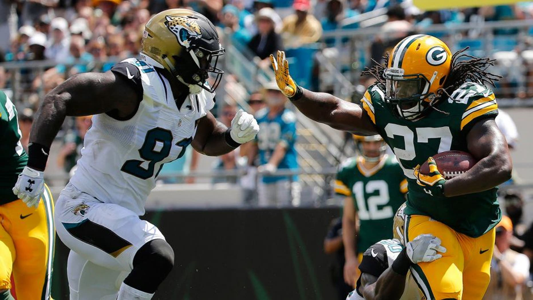 Sep 11, 2016; Jacksonville, FL, USA; Green Bay Packers running back Eddie Lacy (27) runs with he ball as Jacksonville Jaguars outside linebacker Telvin Smith (50) and defensive end Yannick Ngakoue (91) defends during the first half at EverBank Field. Mandatory Credit: Kim Klement-USA TODAY Sports