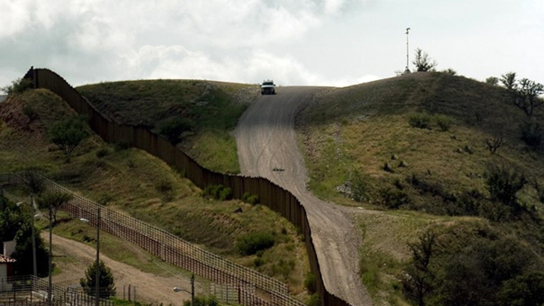 July 28: A U.S. Border Patrol vehicle drives along the fence separating the U.S. from Mexico, near Nogales, Sonora, Mexico.
