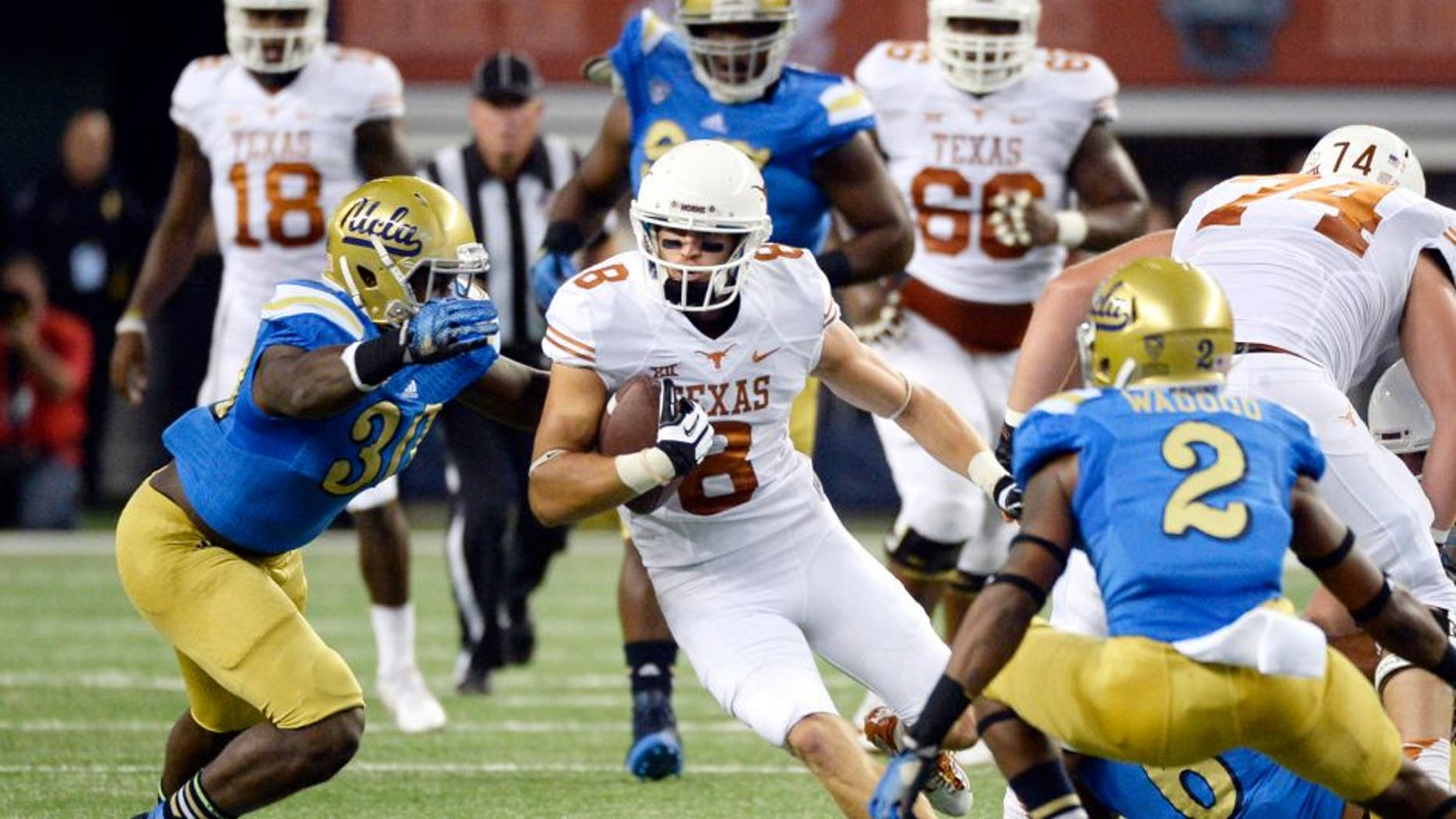Sep 13, 2014; Arlington, TX, USA; Texas Longhorns wide receiver Jaxon Shipley (8) runs against UCLA Bruins linebacker Myles Jack (30) and defensive back Jaleel Wadood (2)during the first quarter at AT&T Stadium. Mandatory Credit: Richard Mackson-USA TODAY Sports