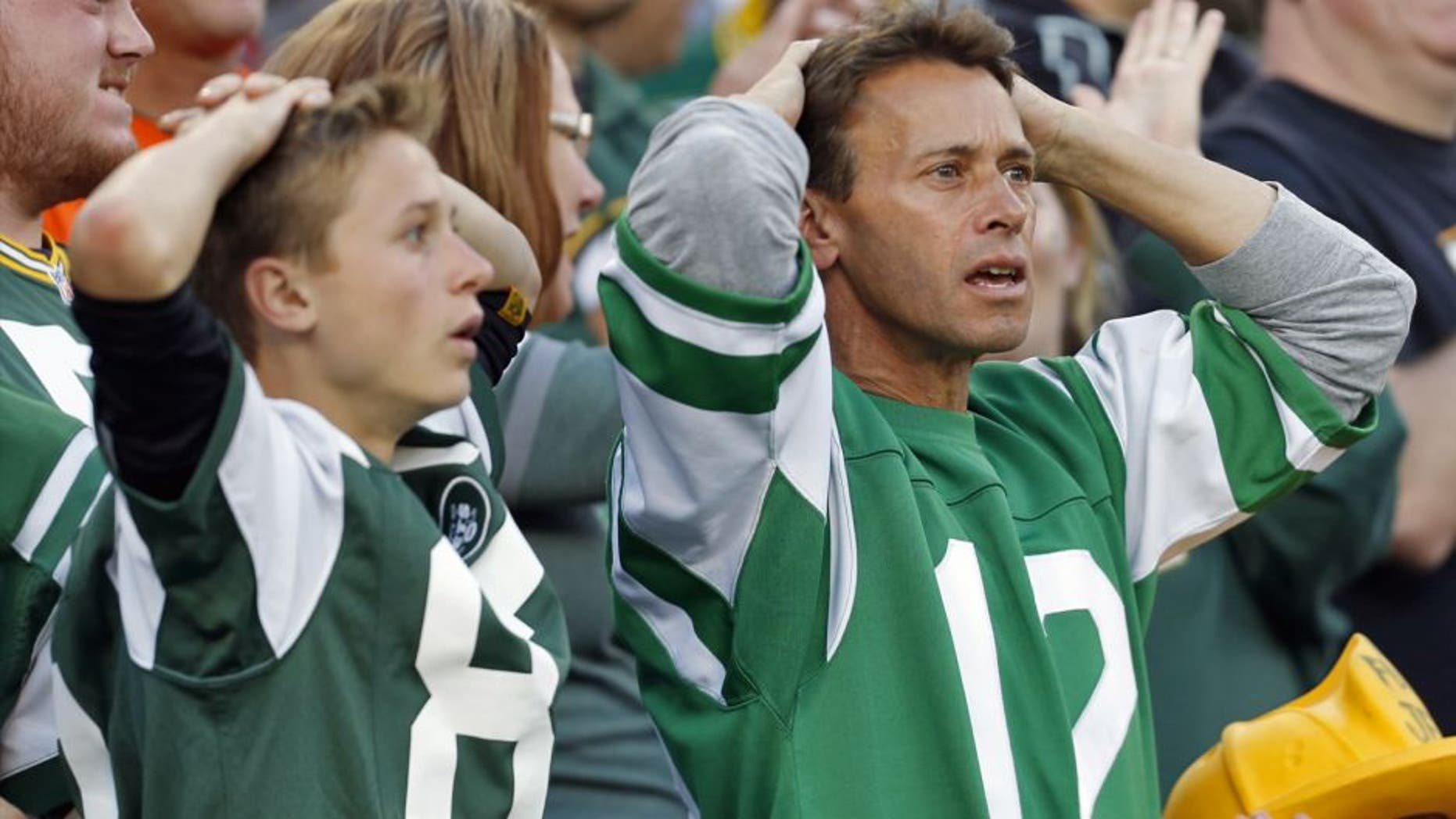 New York Jets fans react after a touchdown catch was called back because the team called a time out before the ball was snapped during the second half of an NFL football game against the Green Bay Packers Sunday, Sept. 14, 2014, in Green Bay, Wis. (AP Photo/Mike Roemer)