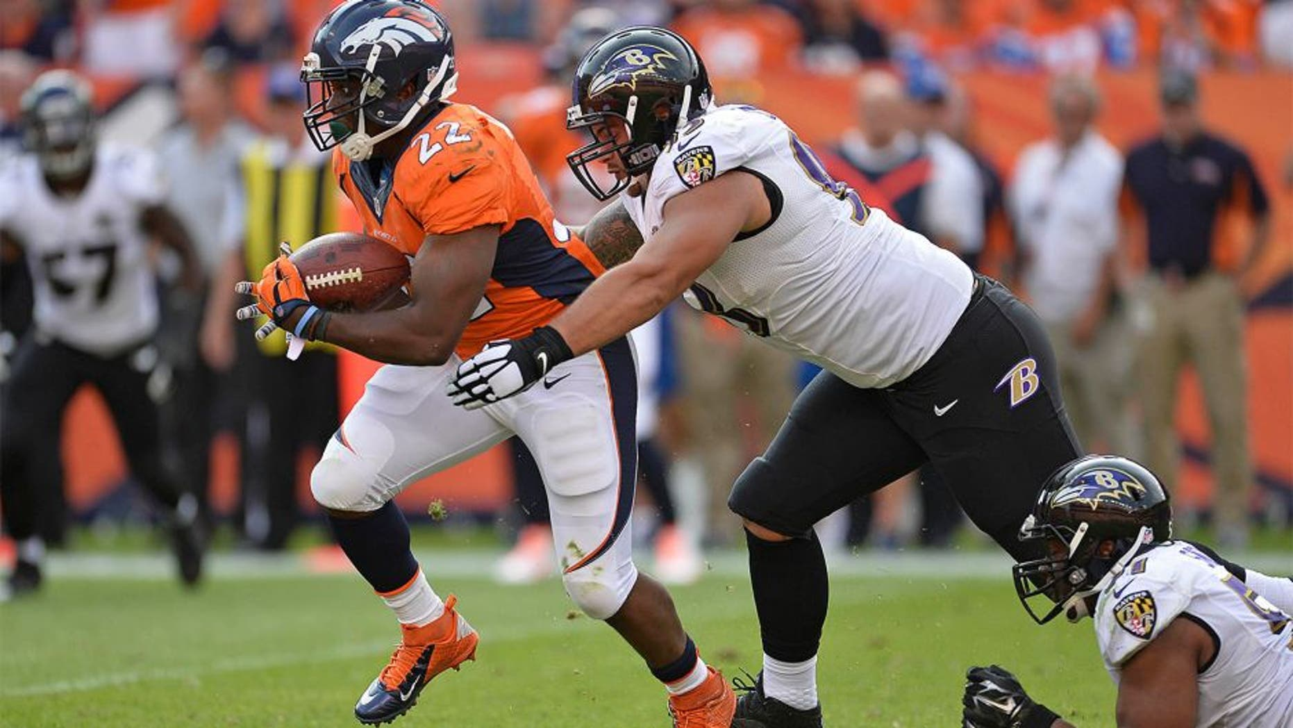 zSep 13, 2015; Denver, CO, USA; Denver Broncos running back C.J. Anderson (22) carries the ball as Baltimore Ravens defensive end Lawrence Guy (93) defends in the fourth quarter at Sports Authority Field at Mile High. The Broncos defeated the Ravens 19-13. Mandatory Credit: Ron Chenoy-USA TODAY Sports