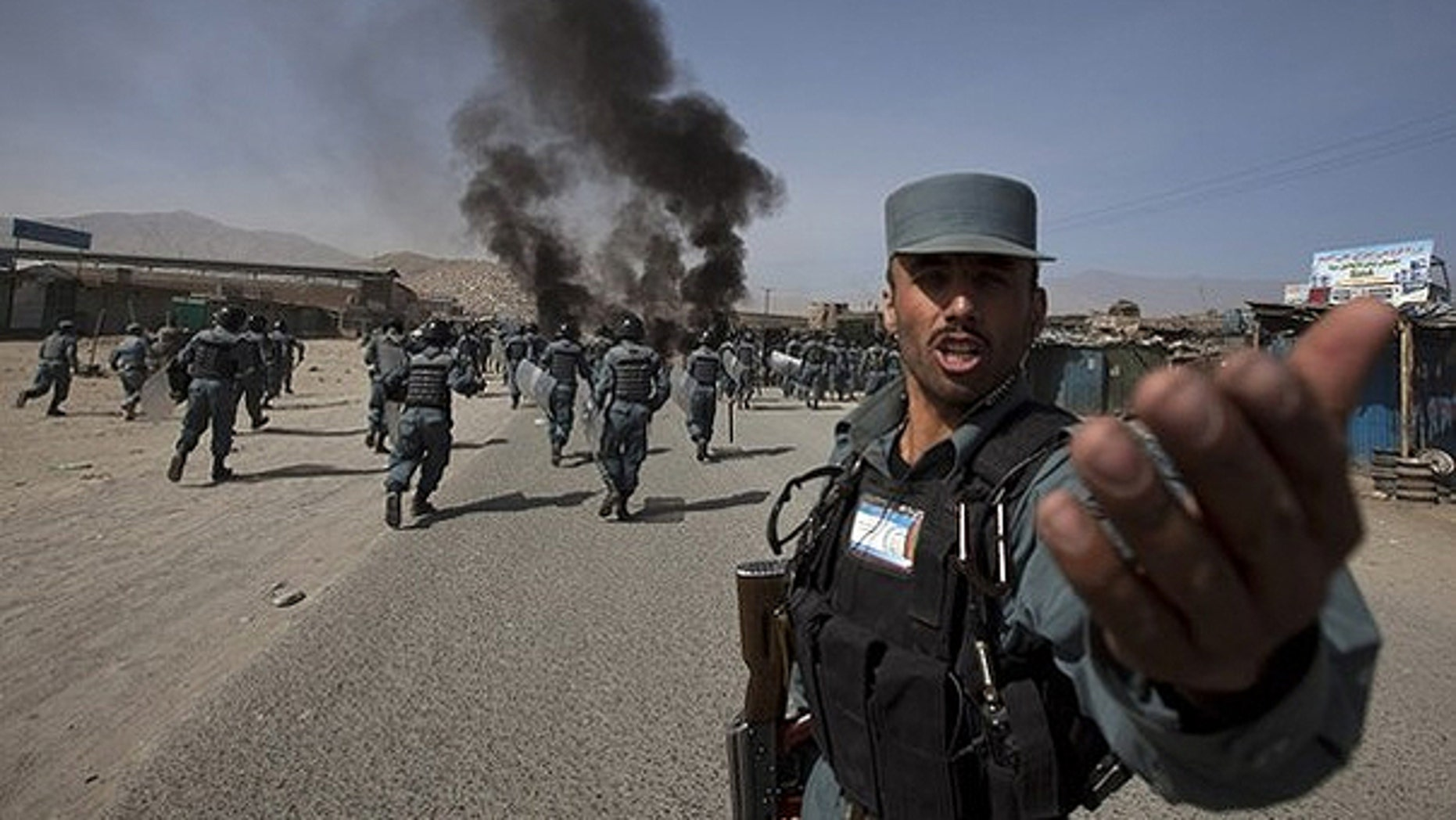 Sept. 15: An Afghan policeman shouts orders as they charge towards protesters in Kabul.