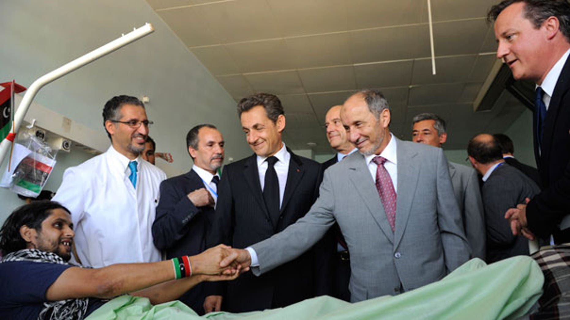 Sept. 15: Leader of Libya's interim government, Mustafa Abdul-Jalil shakes hands with with an unidentified injured man while French President Nicolas Sarkozy, center, and Britain's Prime Minister David Cameron, right, look on in the Tripoli Medical center.