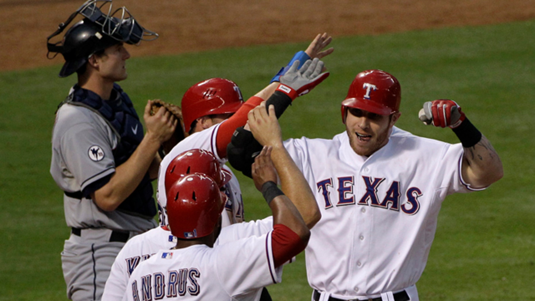 Sept. 14: Cleveland Indians catcher Lou Marson, left, stands by the plate as Texas Rangers' Josh Hamilton, right, is congratulated by teammates Elvis Andrus (1), Ian Kinsler, second from bottom, and Craig Gentry, third from bottom, following Hamilton's grand slam off Indians starting pitcher David Huff in the fourth inning of  a baseball game in Arlington, Texas.